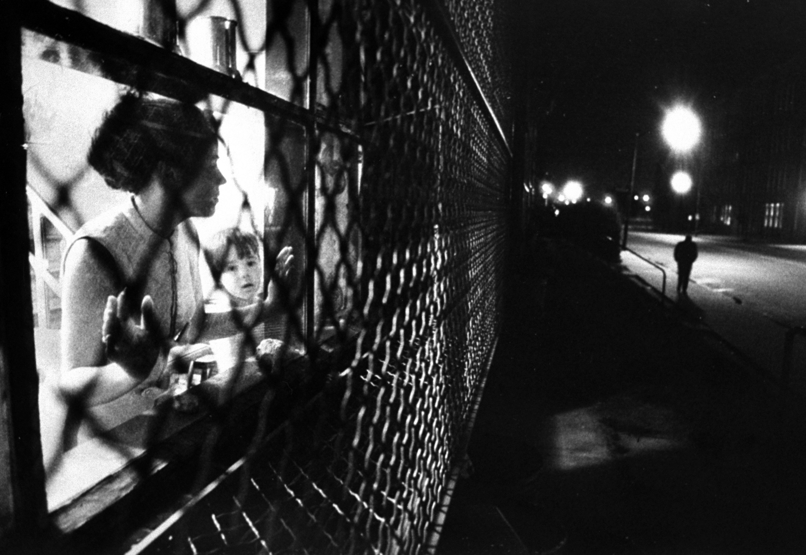 """<b>Caption from LIFE.</b> In a Baltimore ghetto, Mrs. Judy Brookhouser watches from the caged window of her apartment in """"The Compound"""" —the guarded complex operated by Johns Hopkins Hospital for families of staff doctors."""