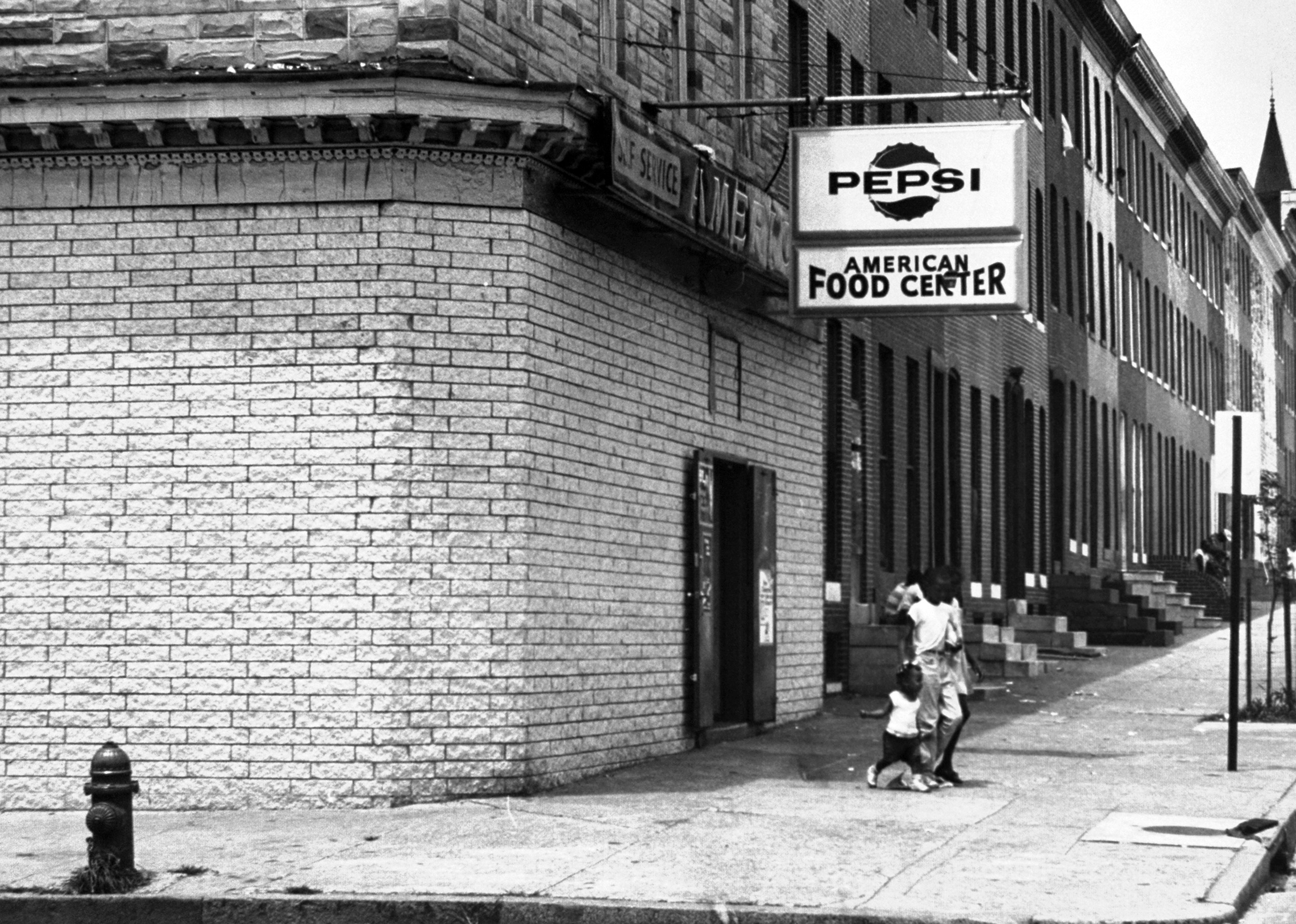 <b>Caption from LIFE.</b> At a grocery, faint outlines around the new brick betray the former presence of shop windows.