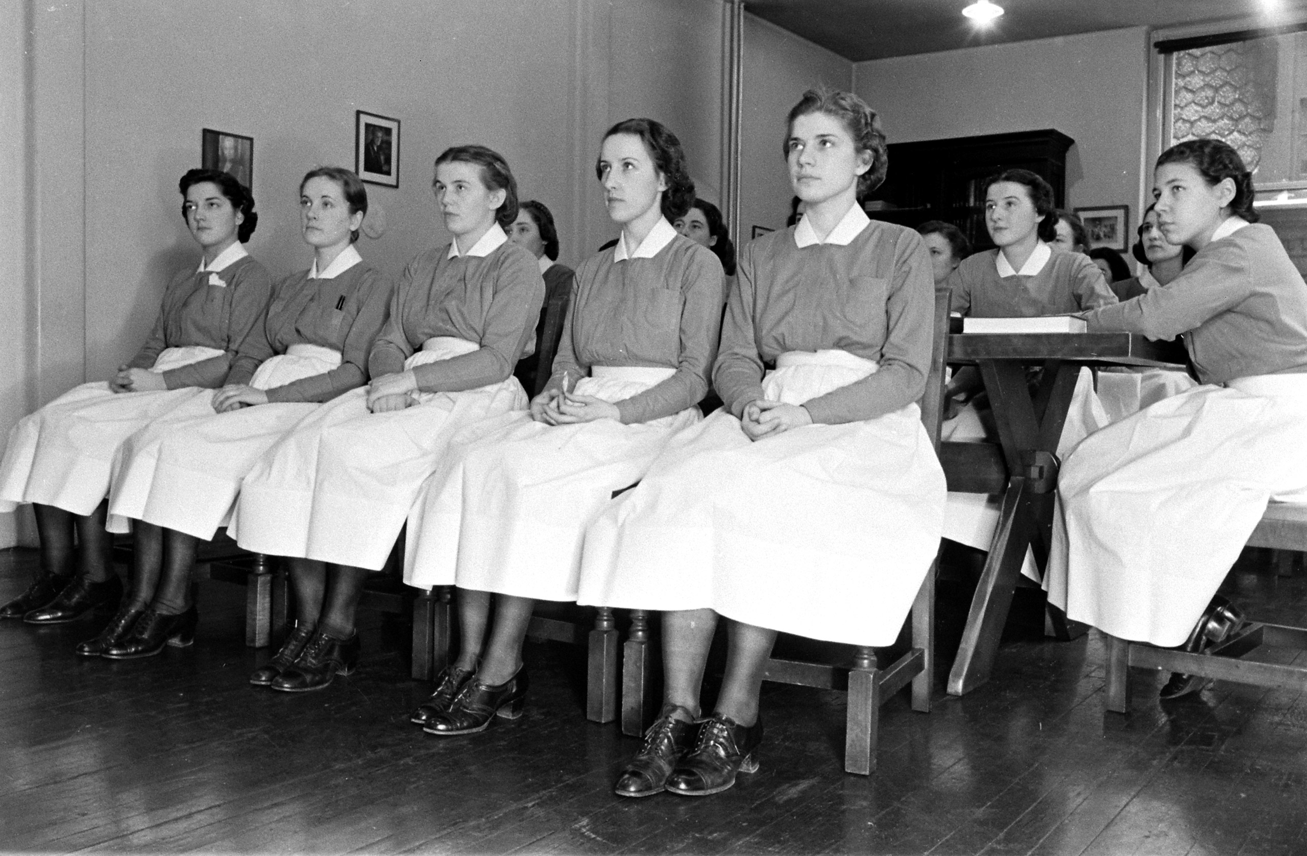 <b>Caption from LIFE.</b> The first two weeks see the new nurse inducted into the ethics of her profession. She listens to talks on life in New York, on living with a group, on the problems of hospital administration. At first she has to buy her own blue uniform, black stockings and low-heeled shoes. After she has been capped, the hospital supplies the uniform.