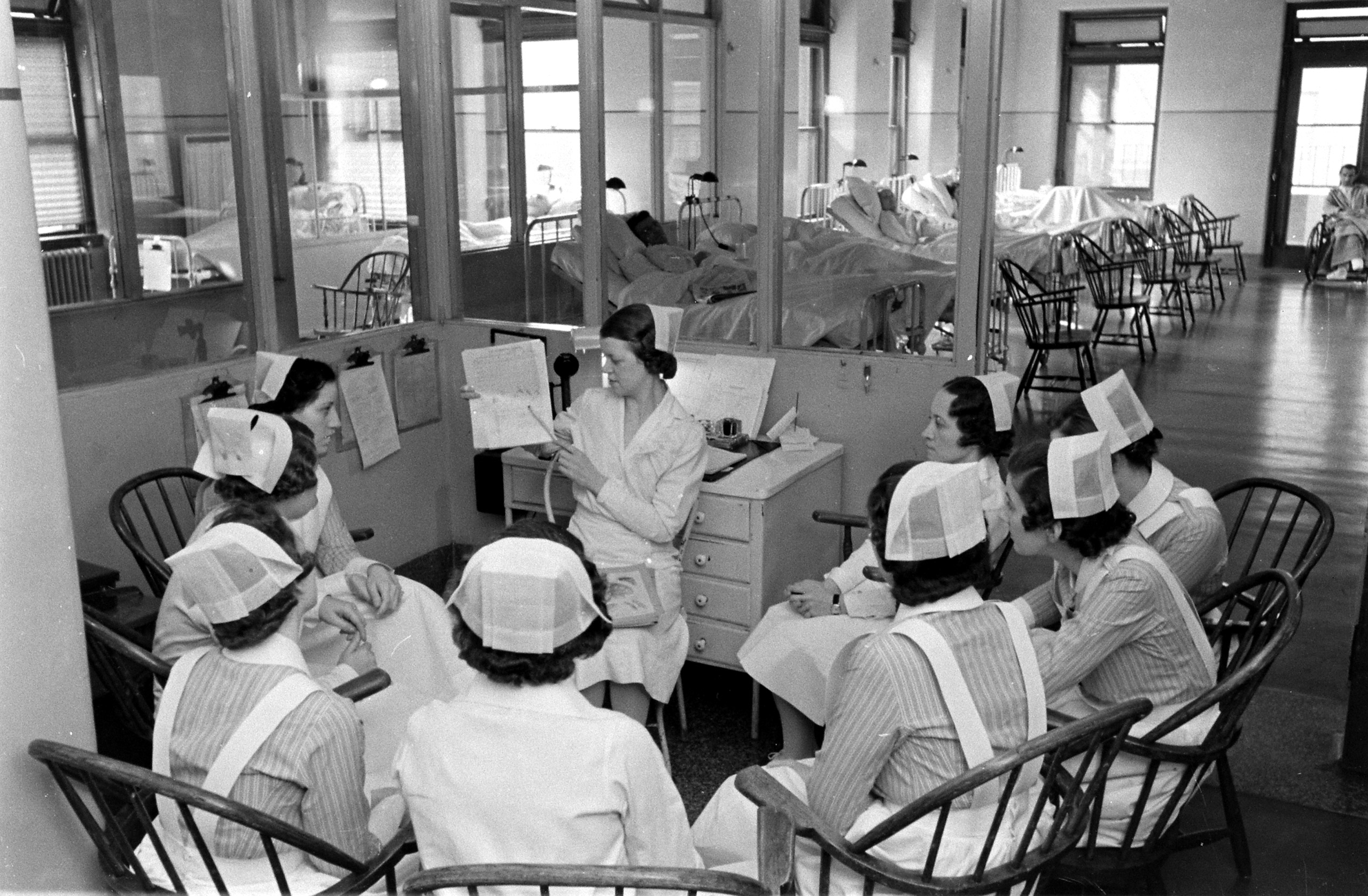 <b>Caption from LIFE.</b> Ward duty begins at 7 am, when nurses meet with the head day nurse (center), who relays to them the report left by the head night nurse. She here explains the chart of a patient in the male surgical ward (in background). Striped garb indicates capped nurses; white uniforms, graduate nurses.