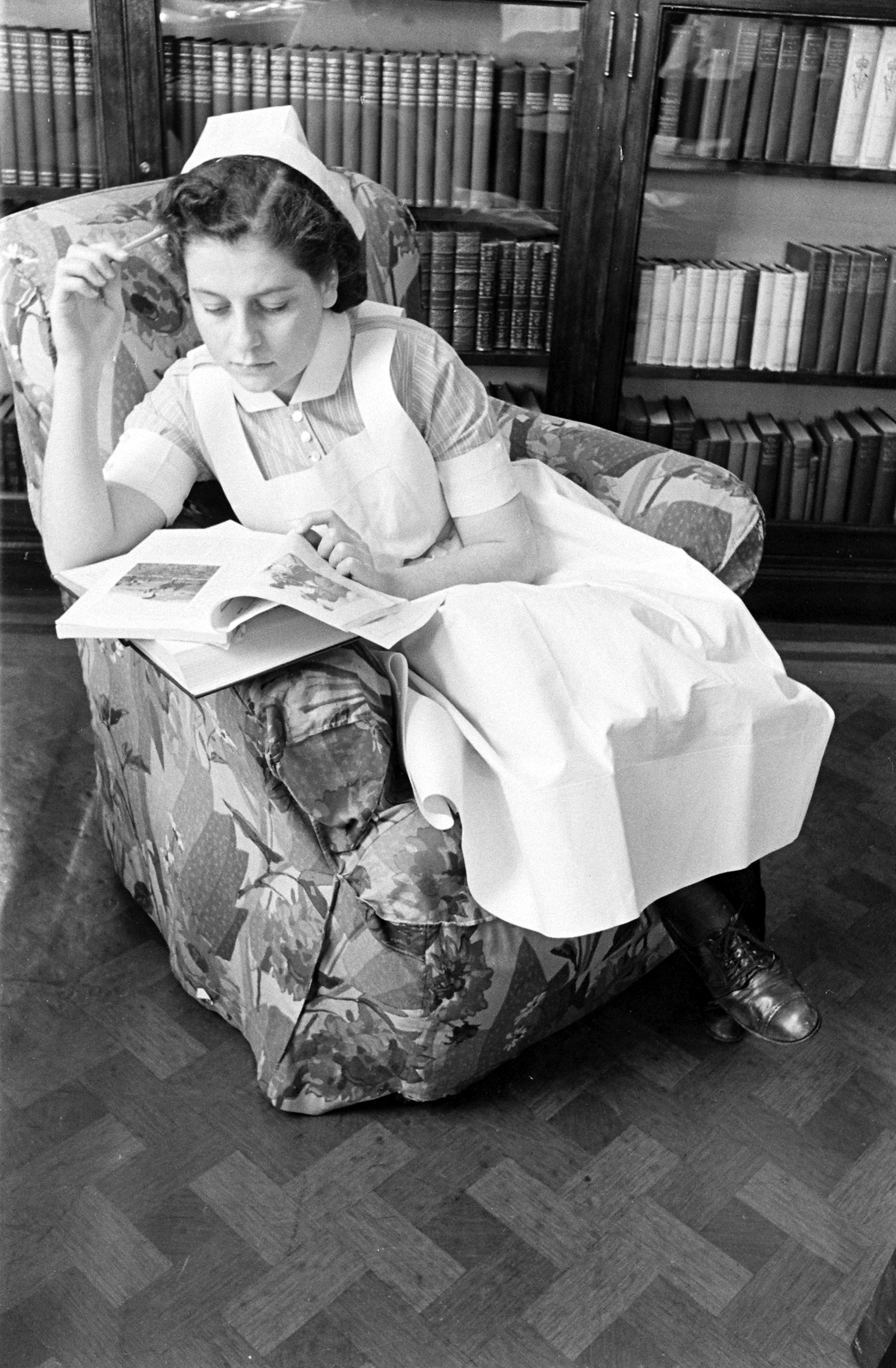 <b>Caption from LIFE.</b> After dinner nurses read in library or dance together in reception room.