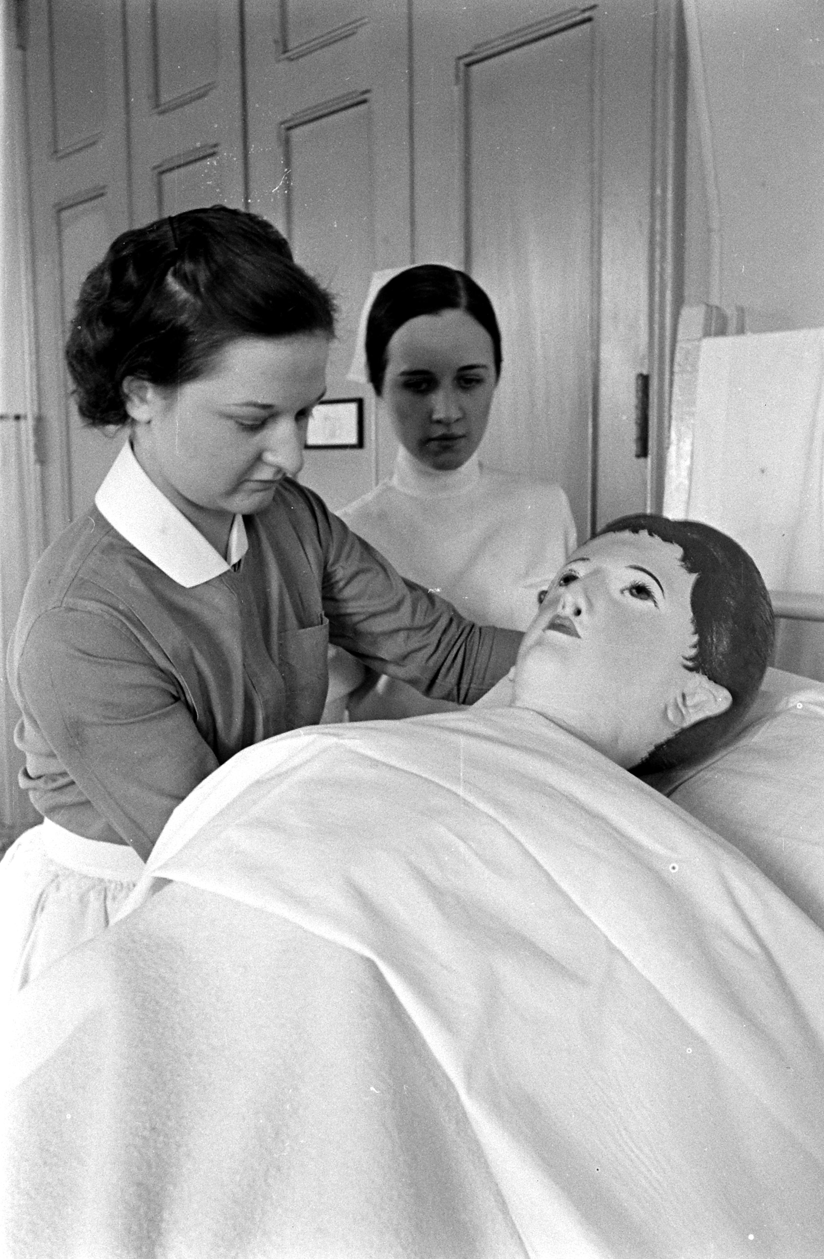 """<b>Caption from LIFE.</b> In the first month the new student learns to make beds. She begins with a dummy known in the Roosevelt Hospital as """"Helen Chase."""" Behind stands instructor in nursing arts."""