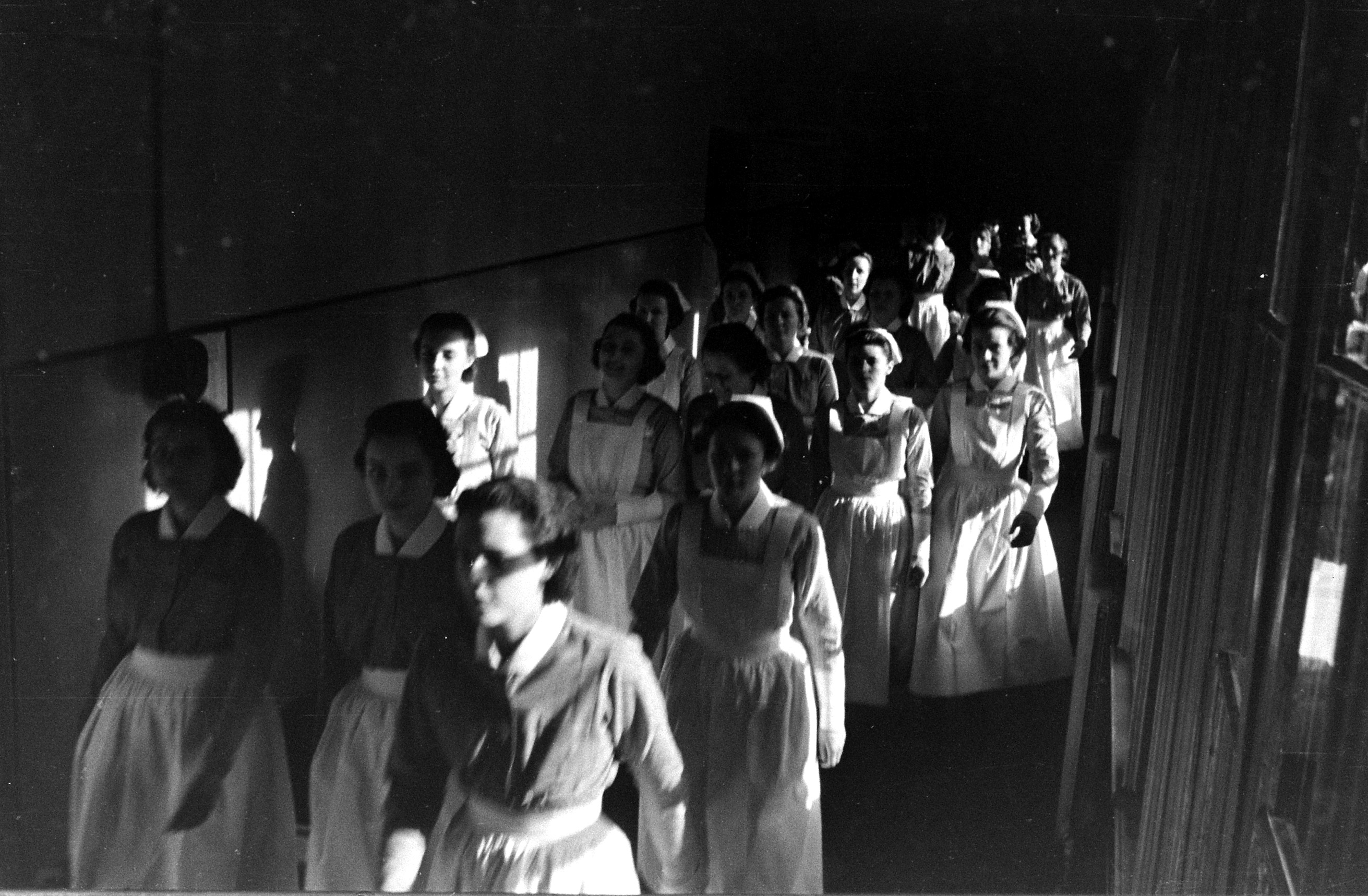 <b>Caption from LIFE.</b> Like nuns, the young student nurses march down the main corridor of the Roosevelt Hospital on their way from classrooms to wards.