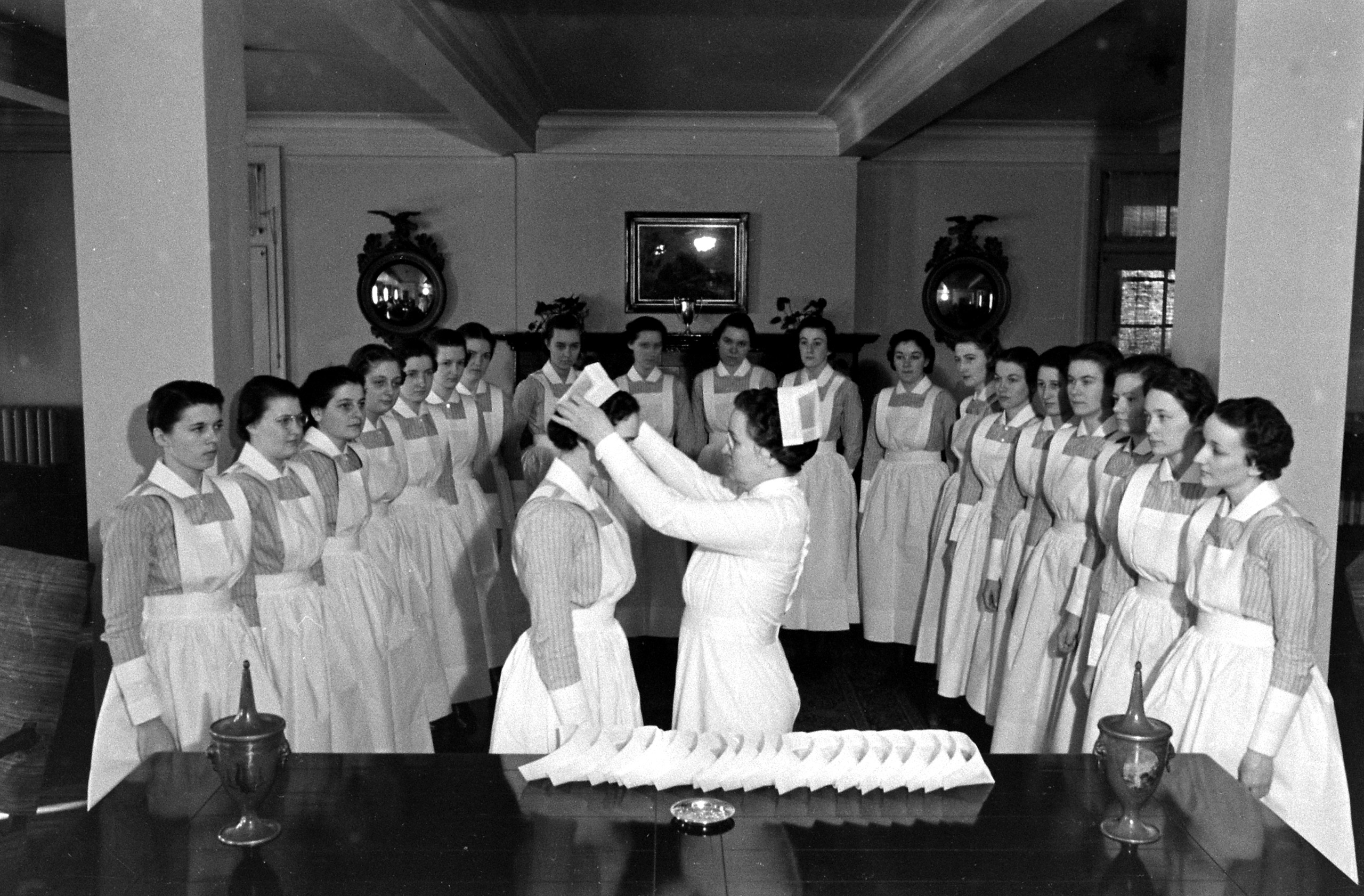"""<b>Caption from LIFE.</b> """"Capping"""" services take place in the reception room of the Nurses' Home. The novices, having successfully passed examinations for their crucial first six months, are now permitted to wear bibbed apron, the striped uniform and the cap of the full-fledged student nurse."""