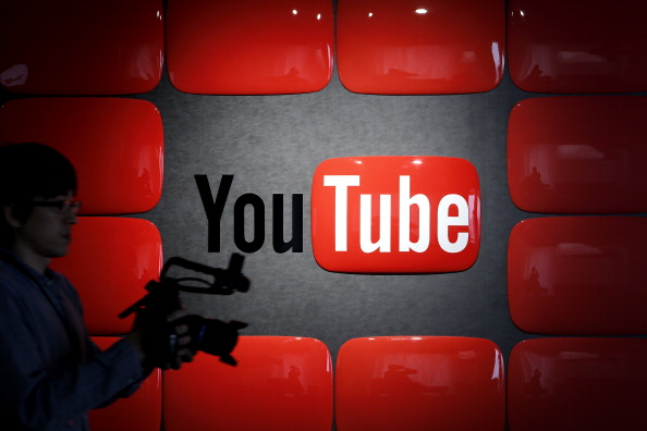 An employee holding recording equipment walks past Google Inc.'s YouTube logo.