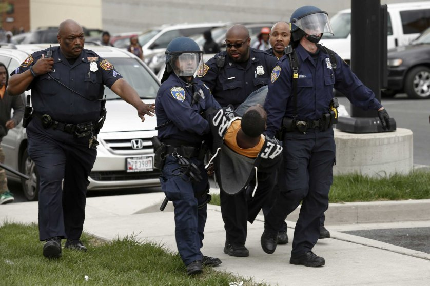 Baltimore Police officers arrest a man following the funeral of Freddie Gray near Mowdamin Mall in Baltimore on April 27, 2015.