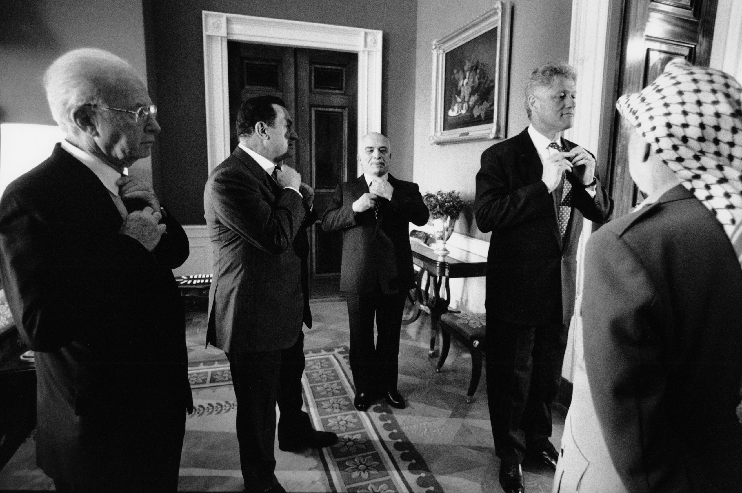 Palestine Liberation Organization leader Yasser Arafat, Israeli Prime Minister Yitzhak Rabin, Egyptian President Hosni Mubarak and King of Jordan Hussein bin Talal take a cue from President Bill Clinton, all adjusting their ties before the ceremony to sign an accord expanding Palestinian self-rule in the West Bank, Sept. 28, 1995.