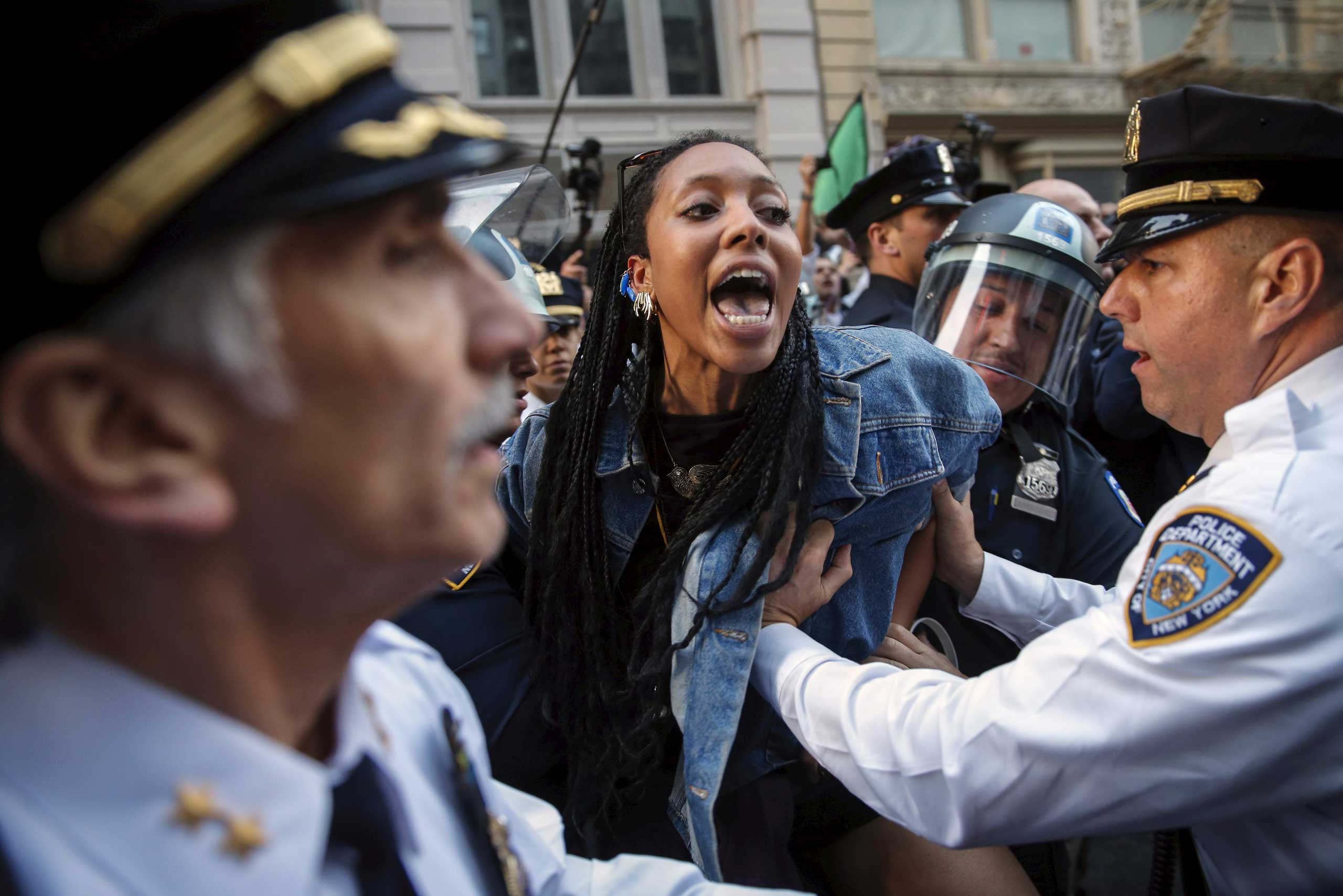New York Police Department officers detain a protester during a march through the Manhattan borough of New York City on April 29, 2015.