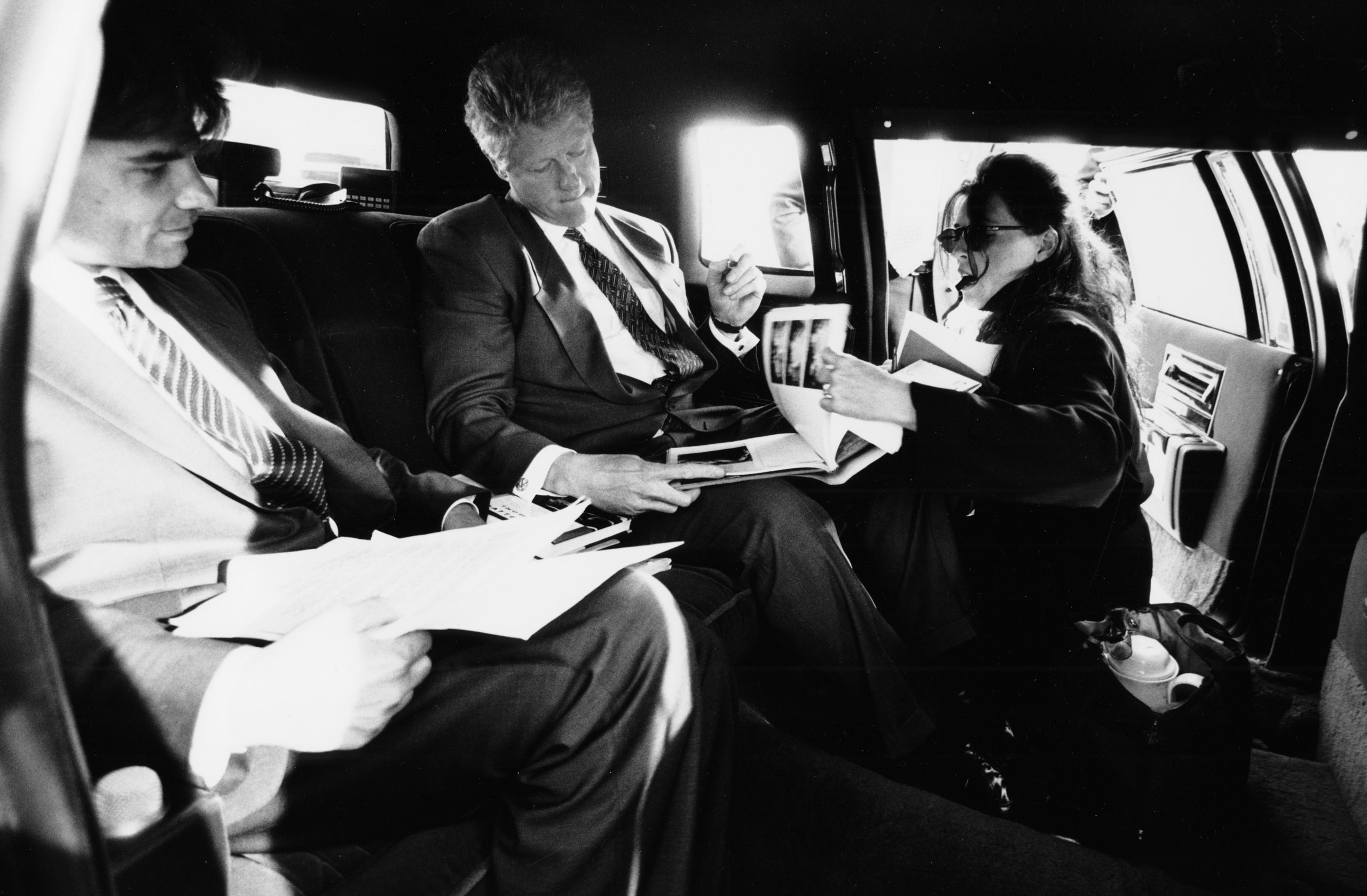 President Clinton in a limousine with George Stephanopoulos and Wendy Smith, signing autographs during a Presidential trip