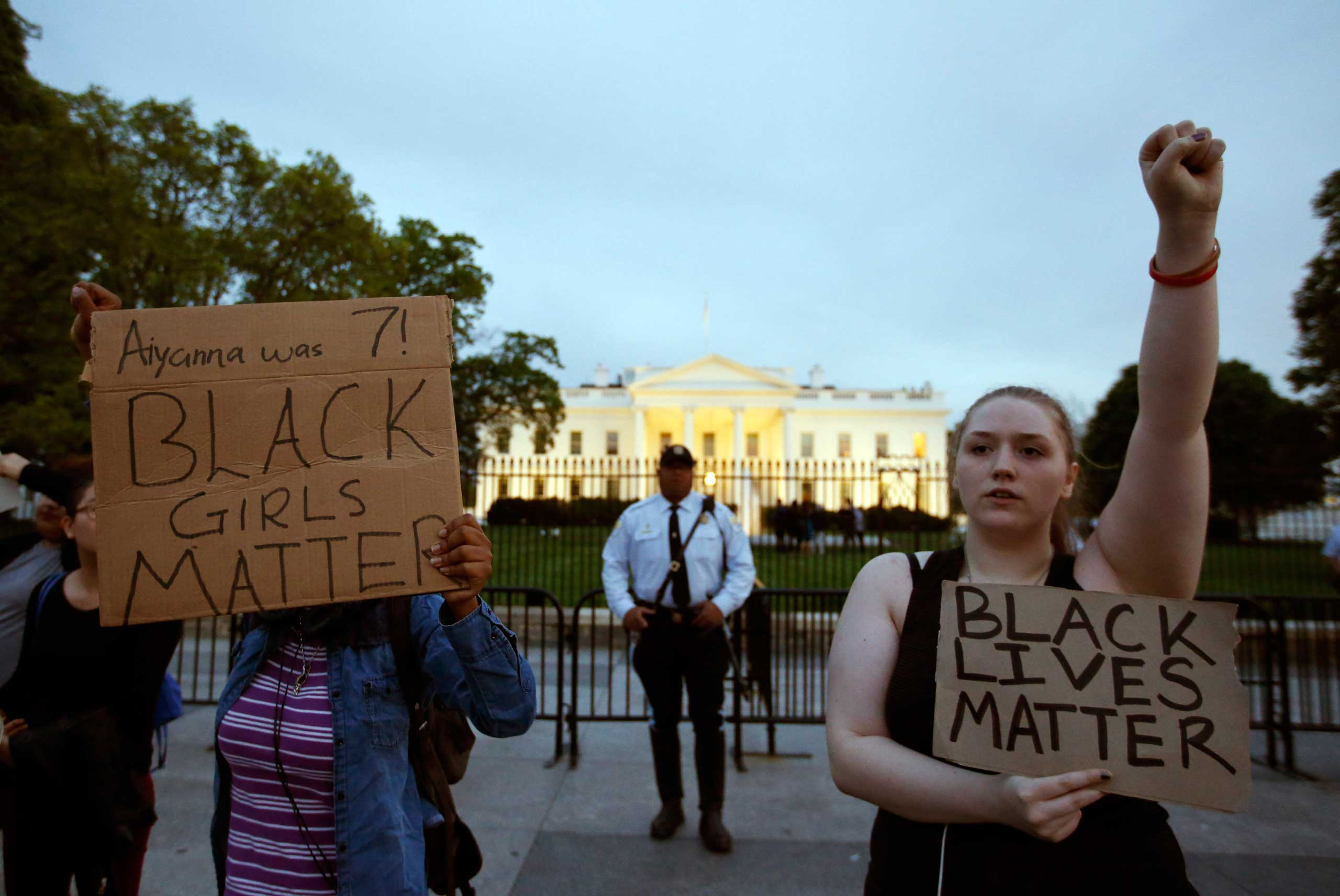 Protestors hold signs during a protest to support the rallies in Baltimore, in front of the White House in Washington on April 29, 2015.