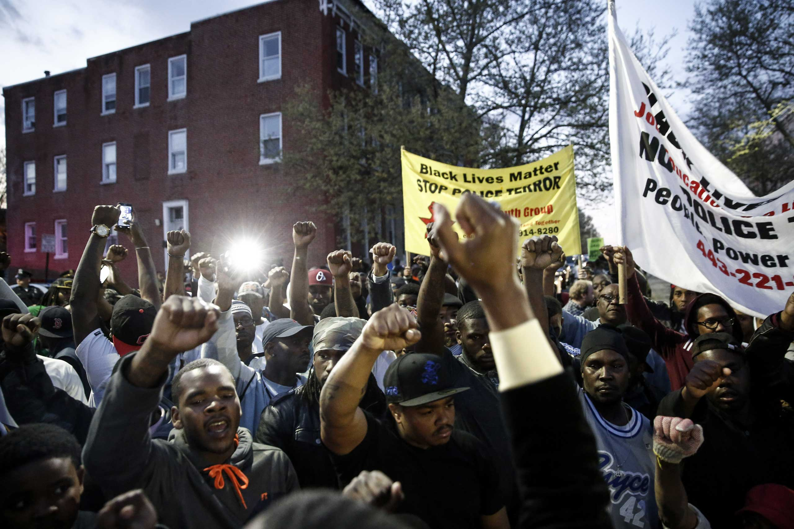 Protestors participate in a vigil for Freddie Gray down the street from the Baltimore Police Department's Western District police station in Baltimore on April 21, 2015.
