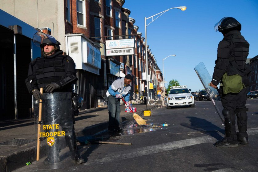 Maryland state troopers stand guard as residents clean up after a night of riots in Baltimore on April 28, 2015.