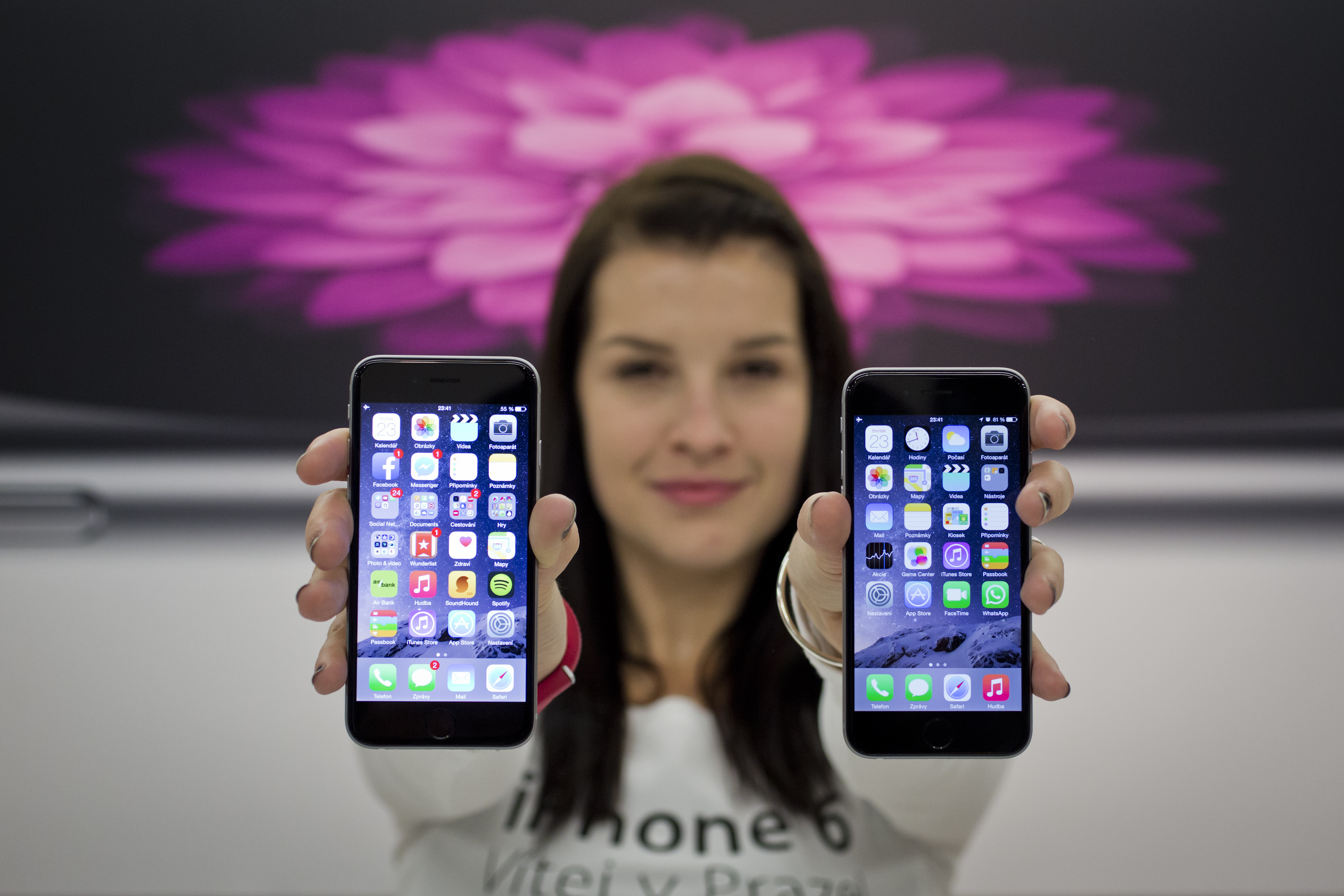 A seller poses with iPhone 6 during a midnight sale of the new iPhone 6 and 6 Plus at Apple Premium Reseller store on October 24, 2014 in Prague, Czech Republic.