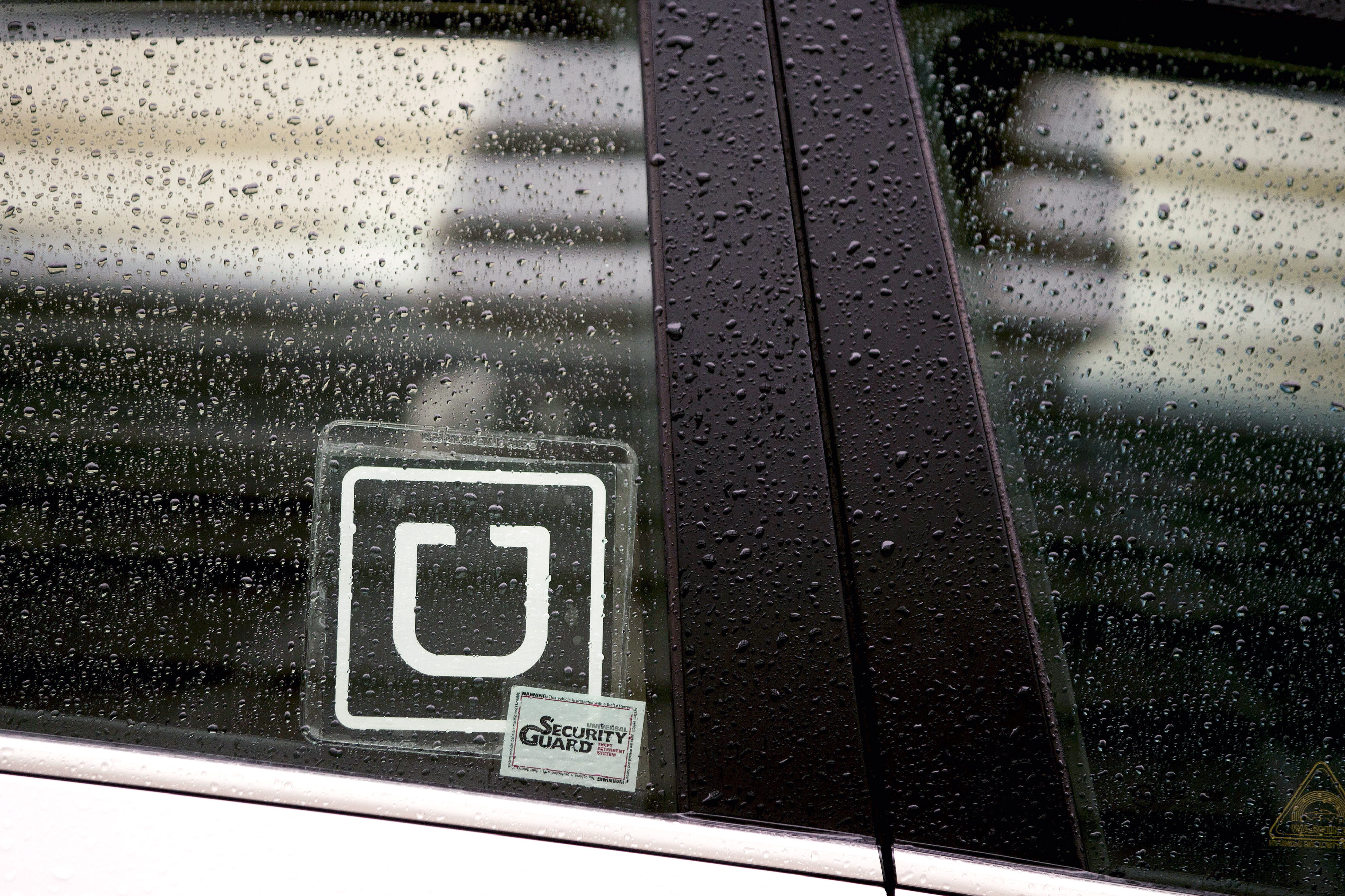 The Uber Technologies Inc. logo is displayed on the window of a vehicle after dropping off a passenger at Ronald Reagan National Airport (DCA) in Washington, D.C., U.S., on Wednesday, Nov. 26, 2014.