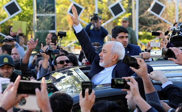 Iranian Foreign Minister Mohammad Javad Zarif greets people as the nuclear negotiating committee arrive at Mehrabat Airport in Tehran on April 3, 2015