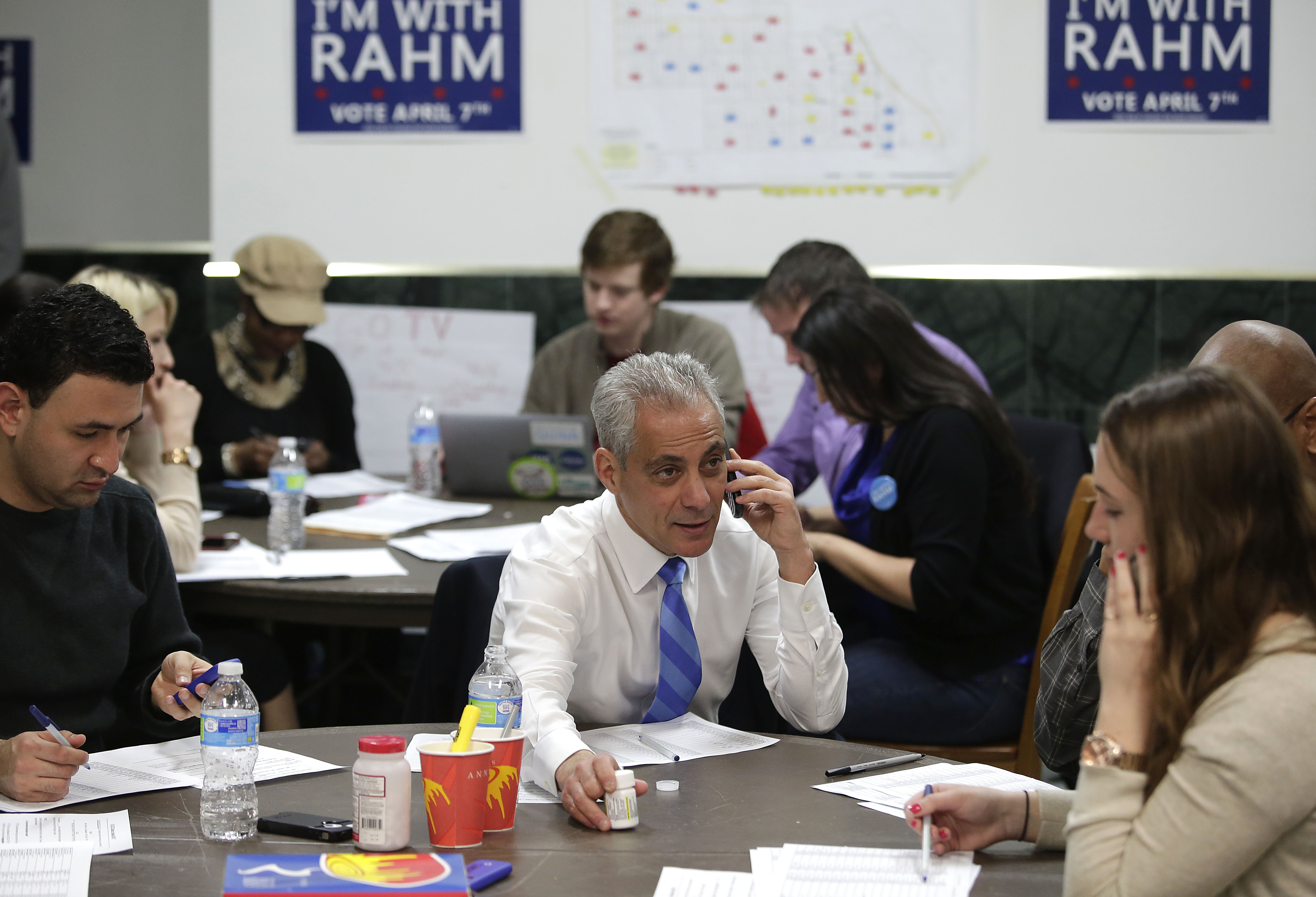 Chicago's mayor and candidate for re-election Rahm Emanuel, center, calla a voter on a mobile phone to remind them to vote during the election as he sits with his campaign workers April 6, 2015 in Chicago, Illinois.