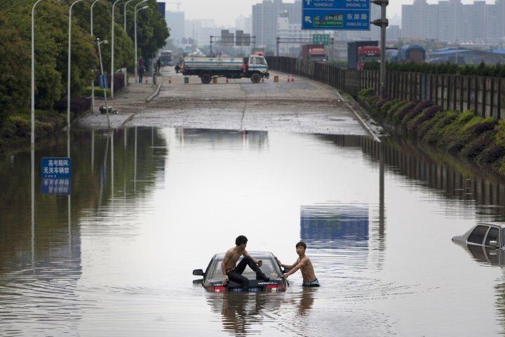 This picture shows two men attempting to push a car out of floodwaters after a storm swept Changsha, central China's Hunan province on taken on April 7, 2015