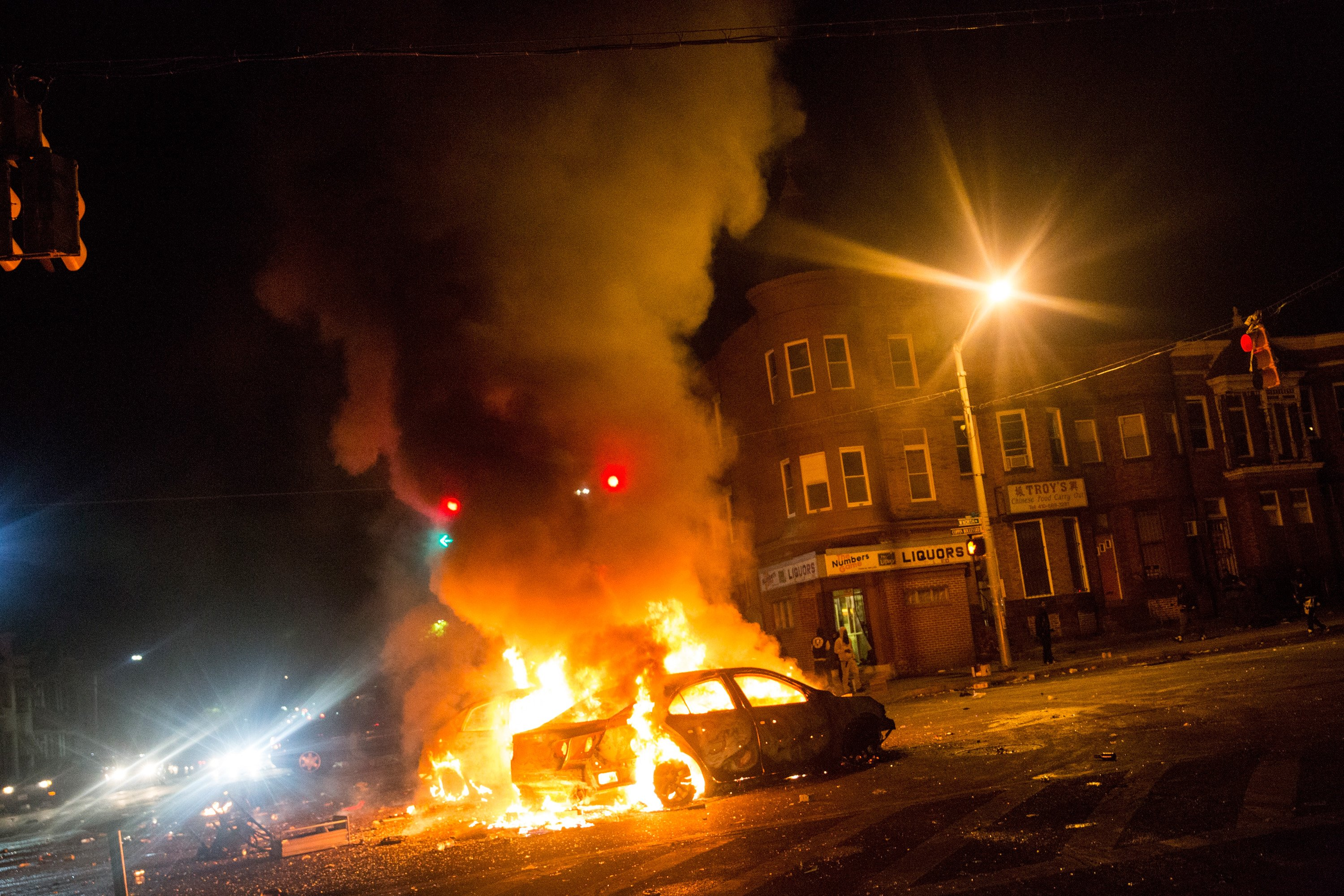 Two cars burn in the middle of an intersection during riots near New Shiloh Baptist Church in Baltimore on April 27, 2015.