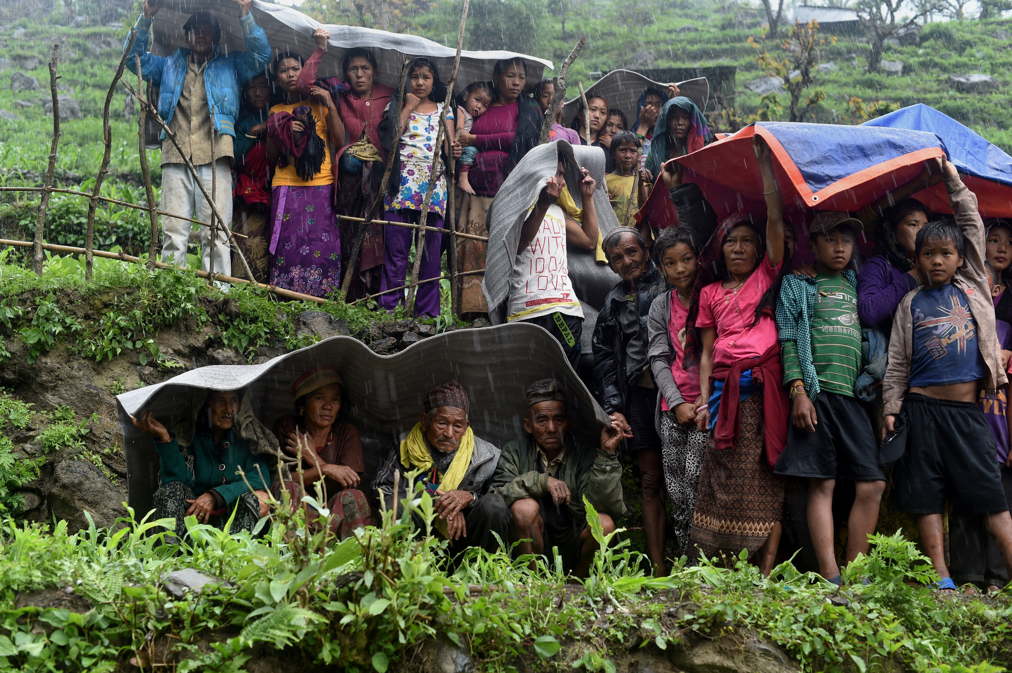 Nepalese villagers shelter from rain as an Indian Army helicopter delivers aid following an earthquake at Lapu in Gorkha on April 28, 2015. The impoverished country's leader said relief workers had still not reached many of the worst-hit areas.