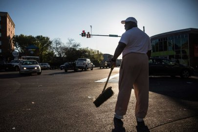 Victor Huntley-el helps clean up debris from a CVS pharmacy that was set on fire yesterday during riots in Baltimore on April 28, 2015.