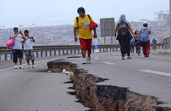 People walk along a cracked road in Iquique, northern Chile, on April 2, 2014 a day after a powerful 8.2-magnitude earthquake hit off Chile's Pacific coast. An 8.2-magnitude earthquake hit Chile late Tuesday, killing at least six people and generating tsunami waves that might ripple as far as Indonesia. AFP PHOTO / ALDO SOLIMANO        (Photo credit should read Aldo Solimano/AFP/Getty Images)