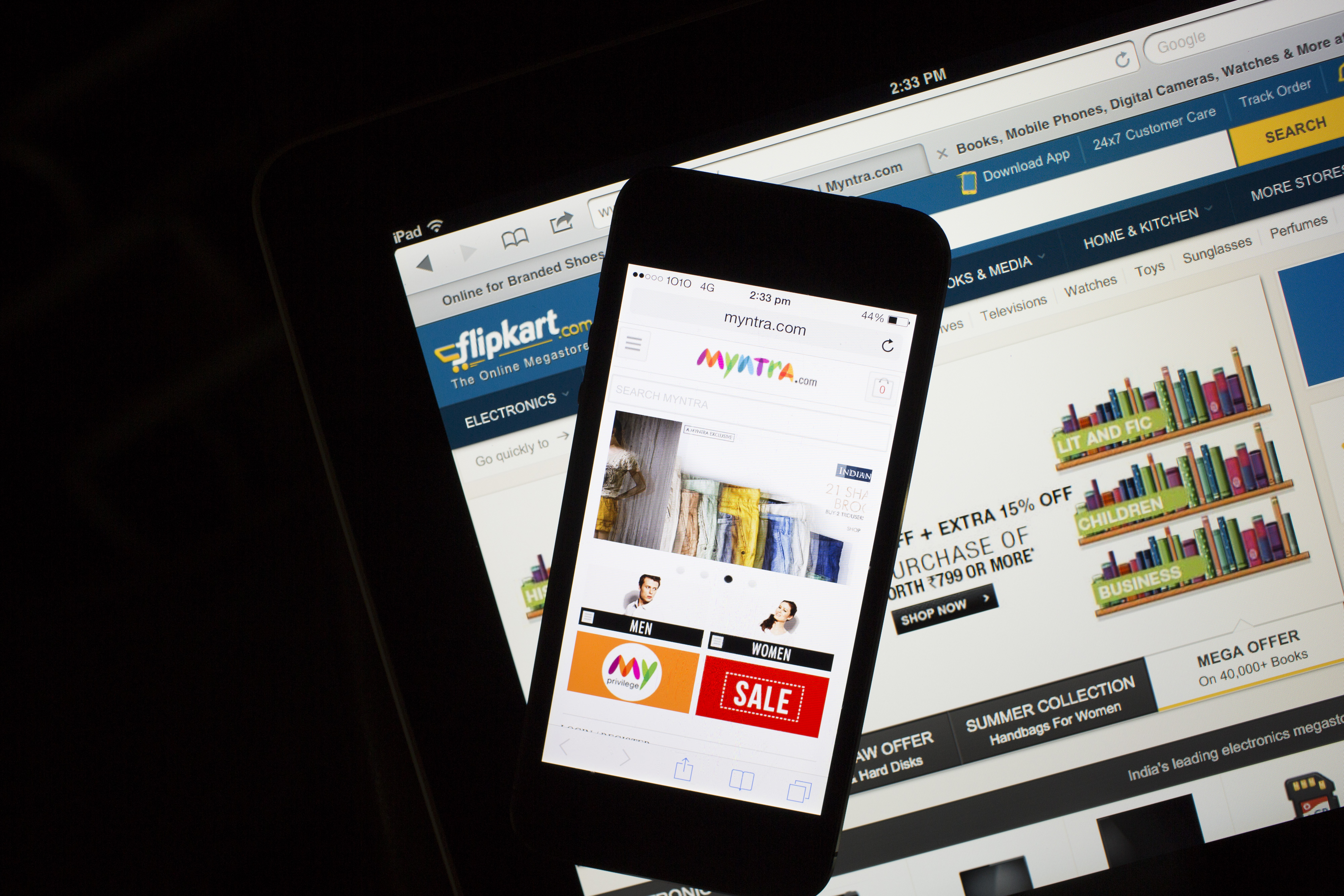 The websites for Flipkart, bottom, and Myntra.com are displayed on an Apple Inc. iPad and iPhone 5c respectively in an arranged photograph in Hong Kong, China, on Wednesday, May 21, 2014.