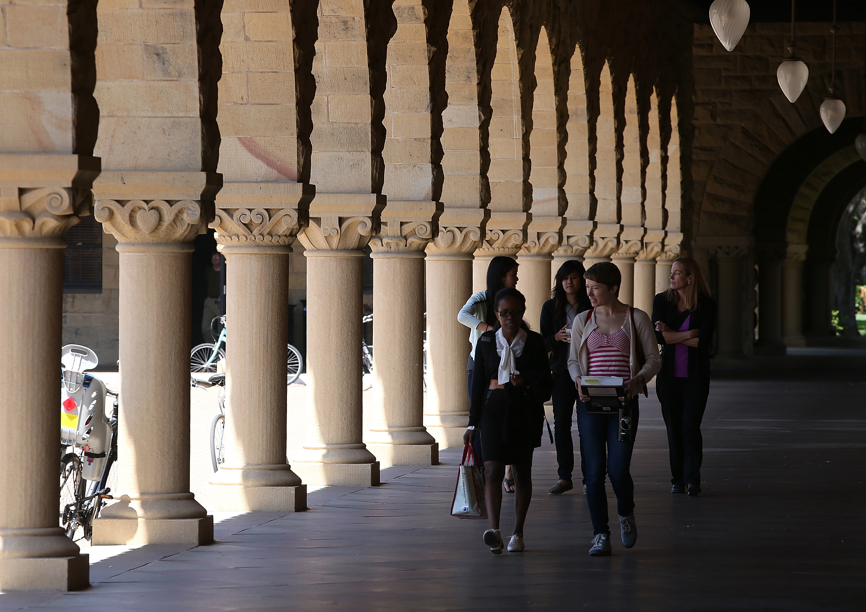 People walk through the Stanford University campus on May 22, 2014 in Stanford, California.