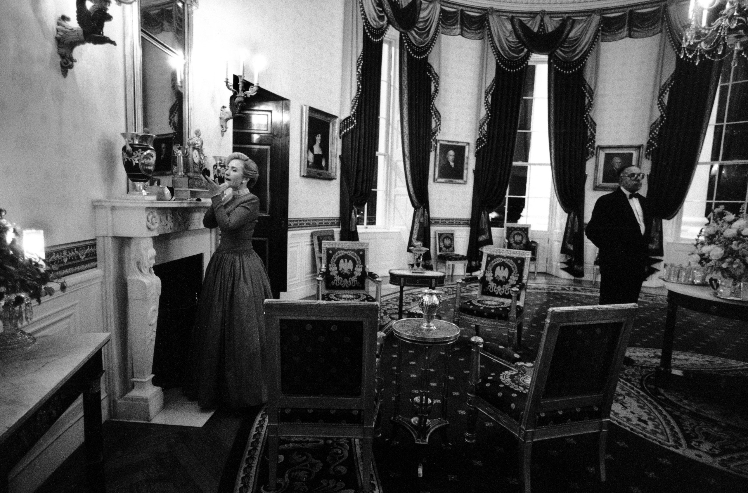 Hillary Clinton does a last-minute touchup in the Blue Room before the 1996 National Governors Association dinner as longtime butler James Jeffries stands nearby, Feb. 4, 1996.