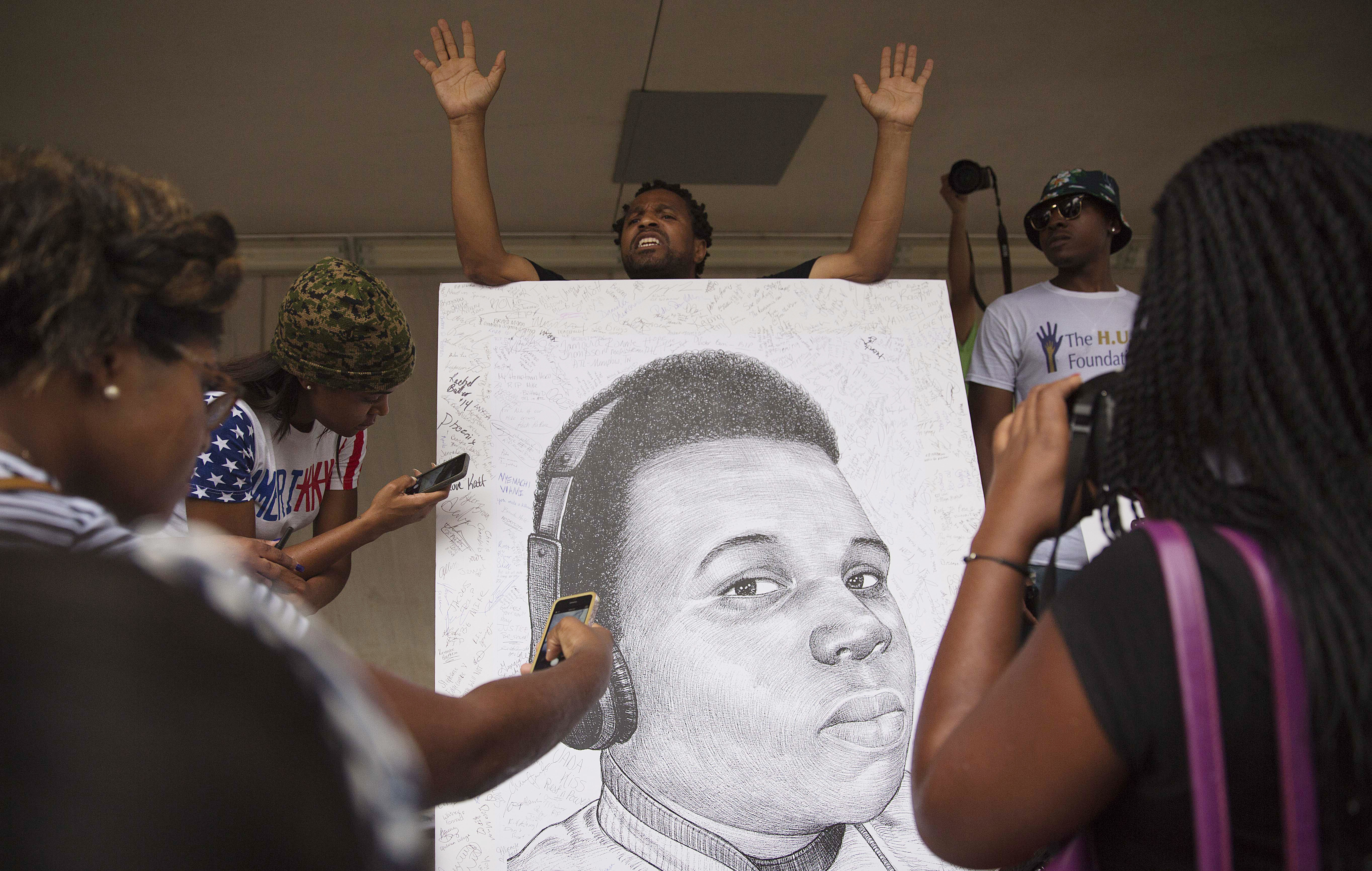 Demonstrators autograph a drawing of Michael Brown during a protest against the fatal police shooting, in Atlanta on Aug. 18, 2014.