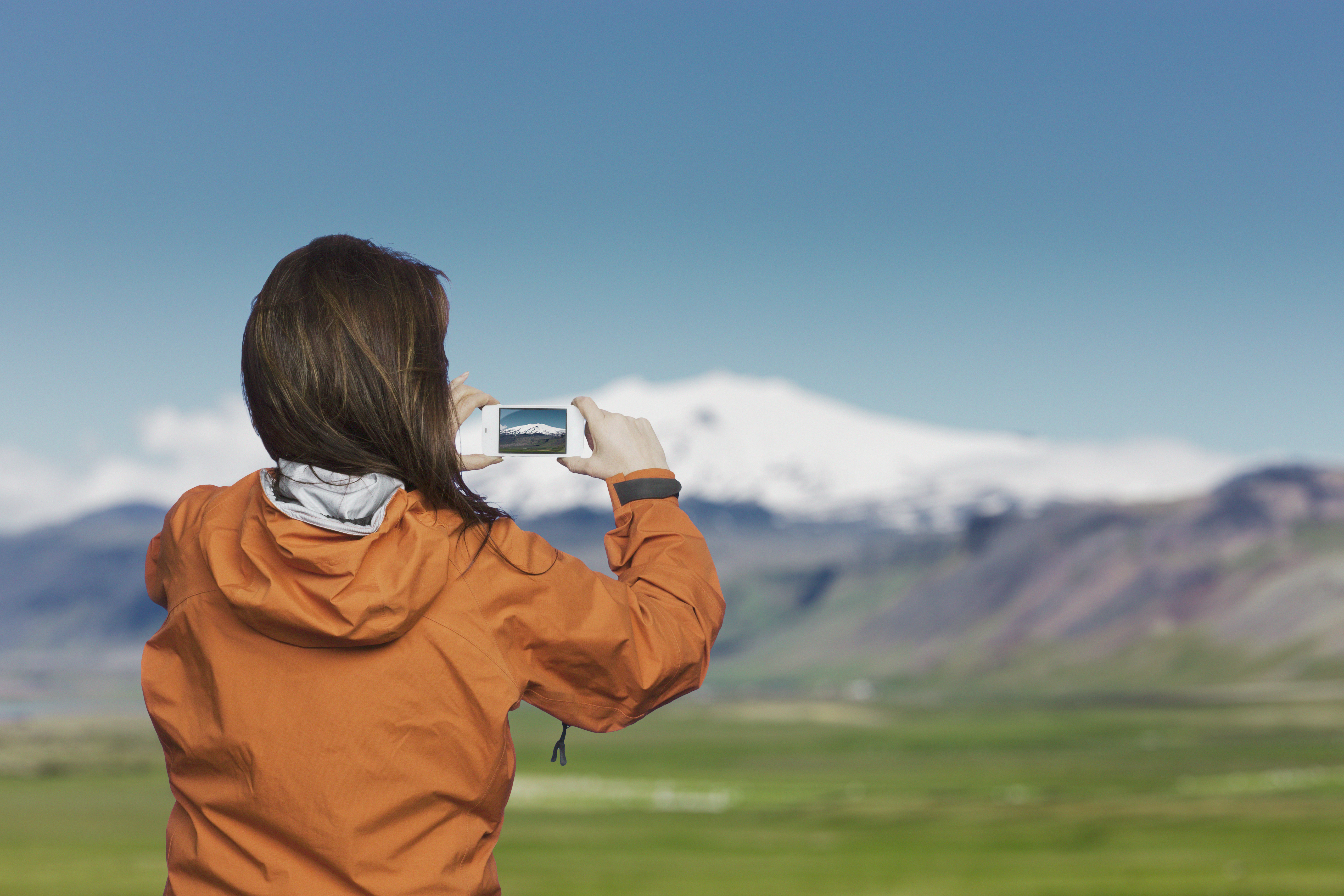 Woman taking picture with smartphone of Snaefellsnes glacier, Iceland