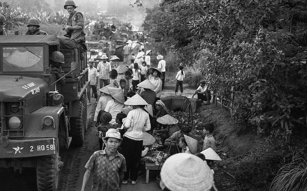 "Convoy, 1967: ""My buddy Sgt. Dick Jackson (with glasses and camera) checks out the crush of villagers as our convoy slows to a crawl.  Anyone in this crowd (including children) might toss a grenade into a truck."""