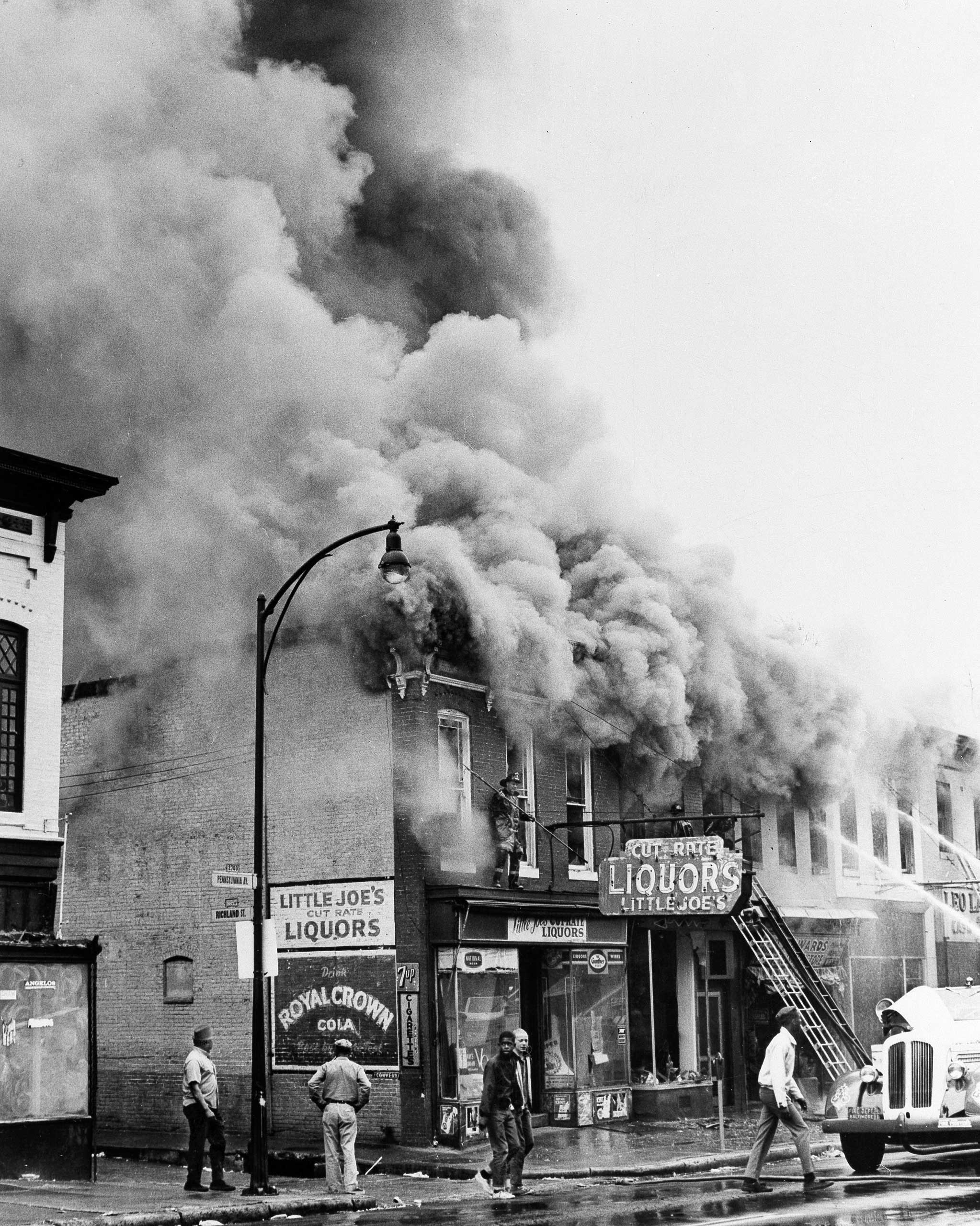 Smoke billows from a liquor store which was looted during the third day of violence, which saw over 400 fires, in Baltimore on April 8, 1968.