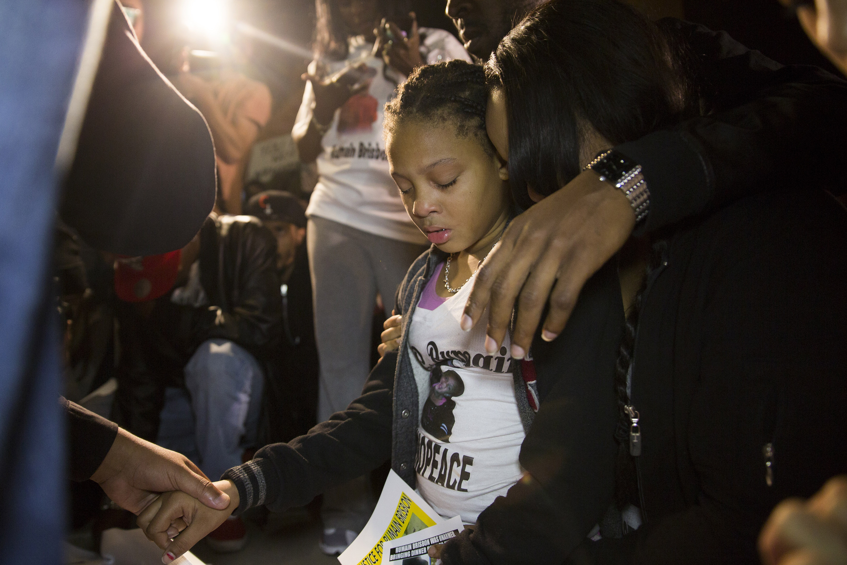 The daughter of Rumain Brisbon (L) begins crying as she kneels in prayer at a vigil for her father who was fatally shot by police, in Phoenix, Ariz. on Dec. 8, 2014.
