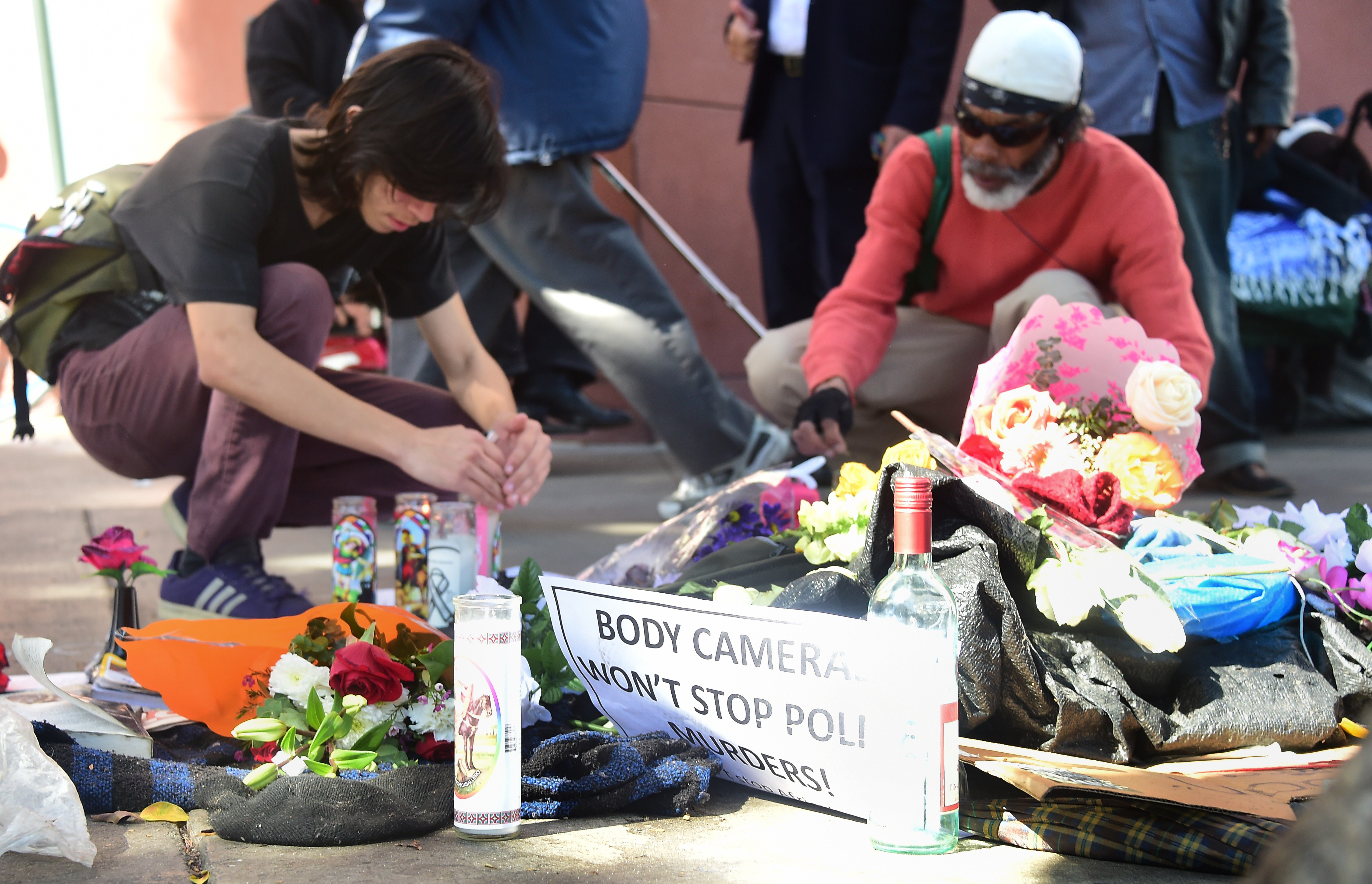 People pay their respects at an ever-growing makeshift memorial where a homeless man known as  Africa  who was shot by police, in Los Angeles on March 3, 2015.