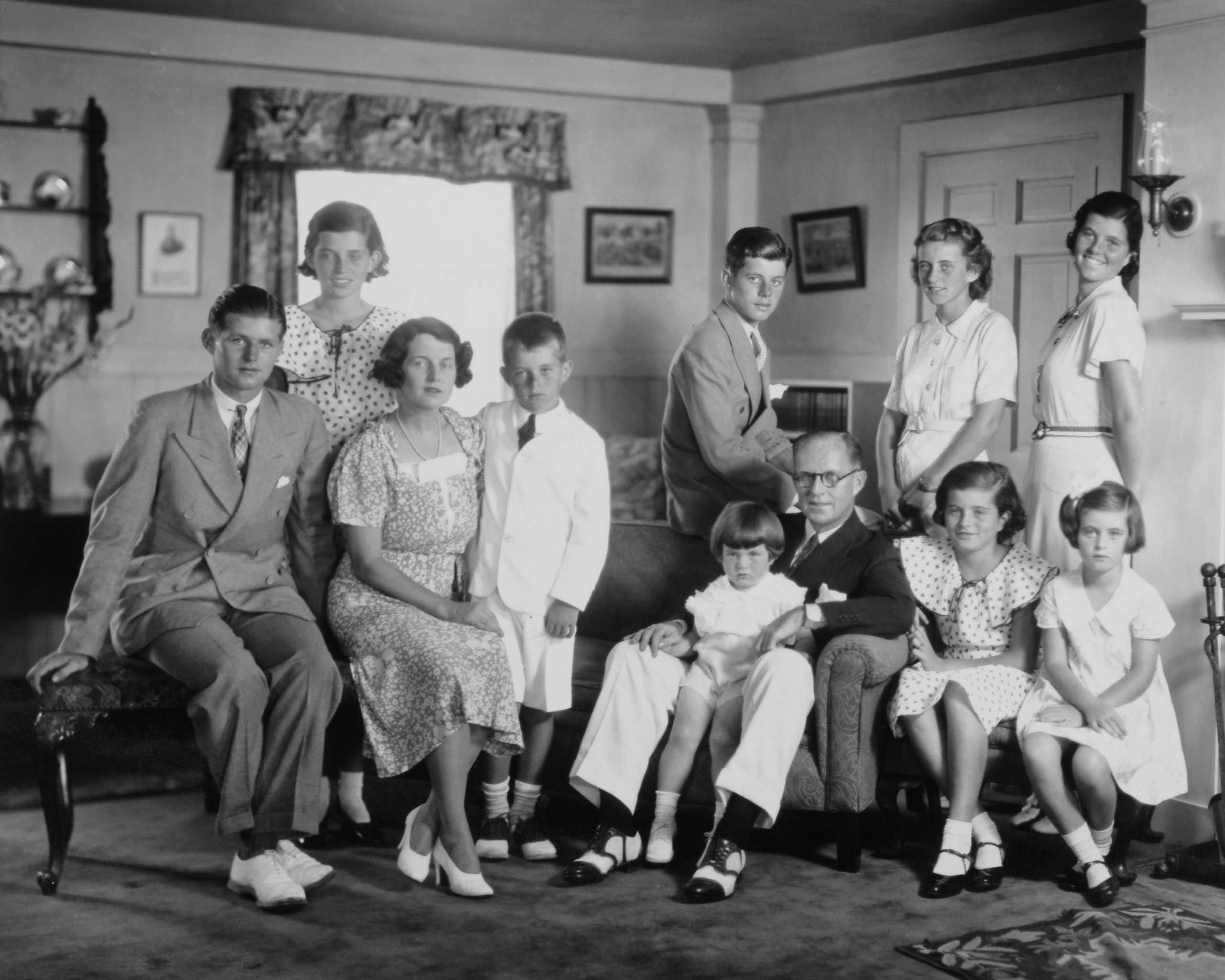 THE KENNEDY FAMILY: The illustrious clan in their Brooklin, Mass., living room, in the 1930s. Front row from left: Joseph P Kennedy Jr (1915 - 1944), Rose Kennedy (1890 - 1995), Robert Kennedy (1925 - 1968), Edward Kennedy, Joseph P Kennedy Sr (1888 - 1969),  Patricia Kennedy (1926 - 2006), Jean Kennedy; back row from left: Eunice Kennedy, John F Kennedy (1917 - 1963), Kathleen Kennedy (1920 - 1948), and Rosemary Kennedy (1918 - 2005)