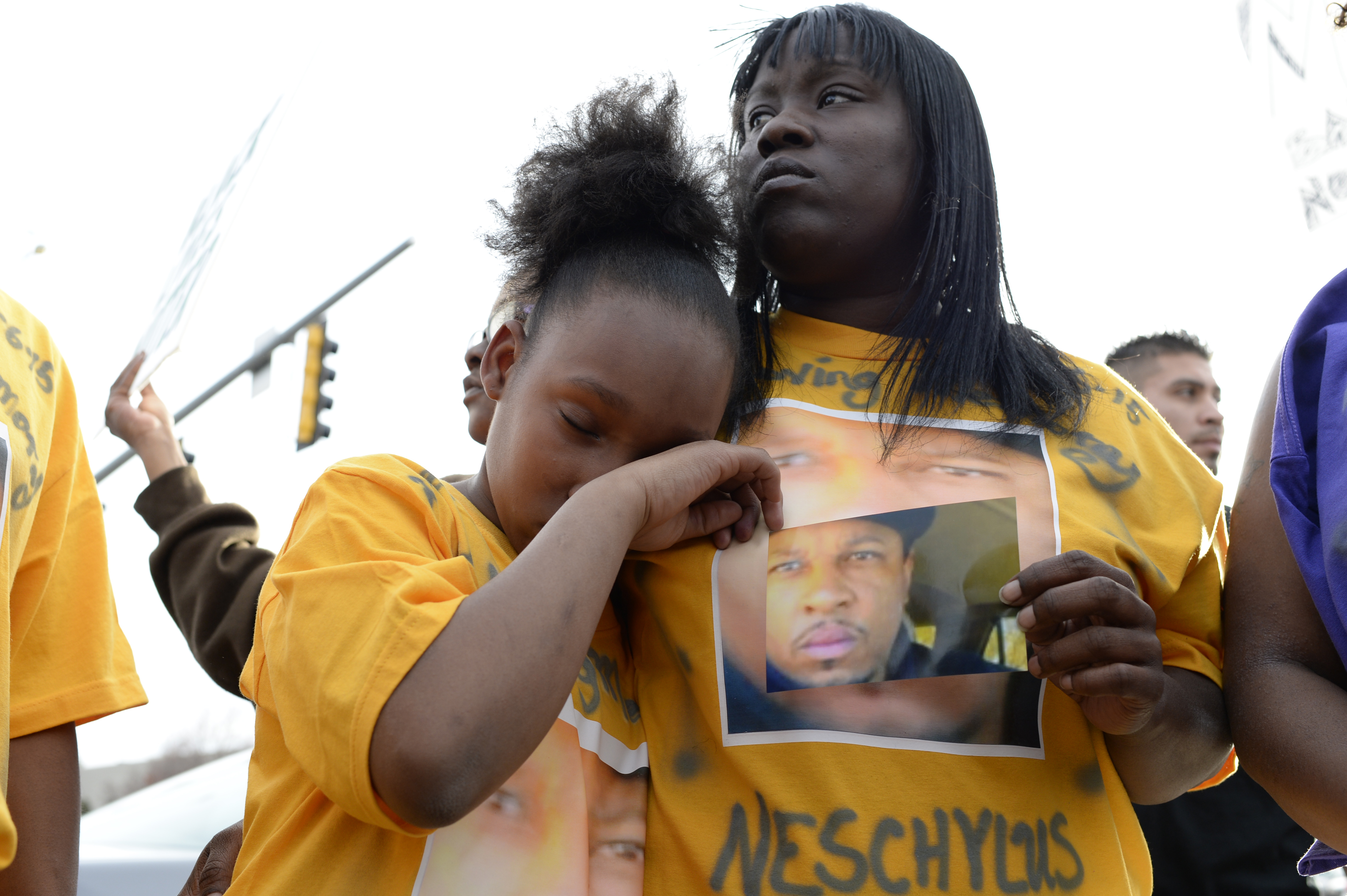 Xiaxong Carter, 10, daughter of Naeschylus Vinzant, wipes away a tear while she holds onto her mother, Laneisha Butler during a protest against the fatal police shooting of her father, in Aurora, Colo. on March 11, 2015.