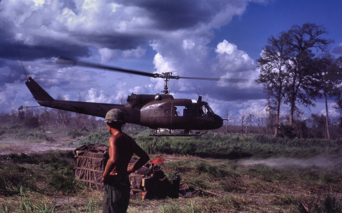 "LZ, 1967: ""Bell UH-1 Iroquois (Huey ""Slick"") helicopter makes a quick troop drop at a Fire Support Base near the Cambodian border without touching down."""