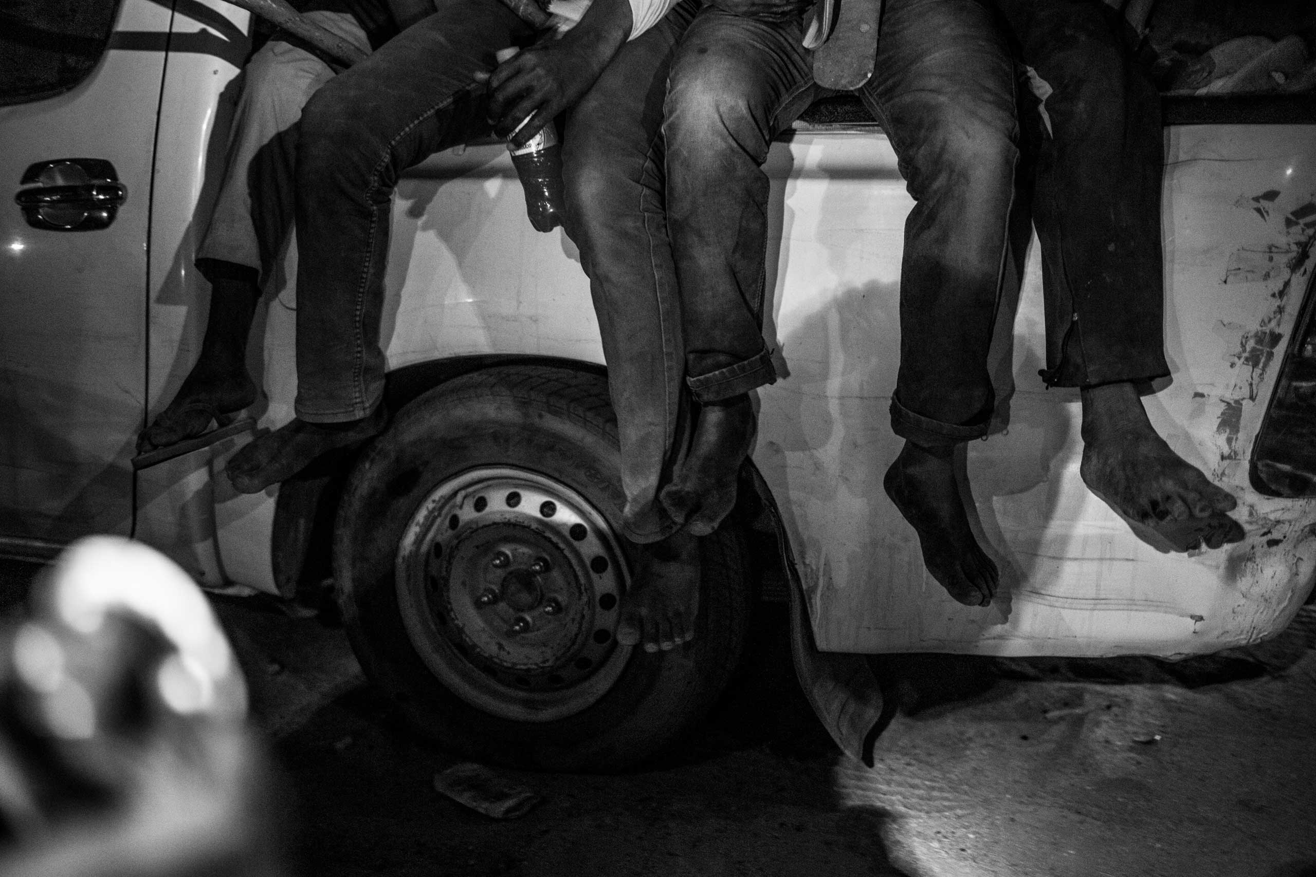 The barefeet of migrants hang from the back of a pickup truck carrying them to Libya.