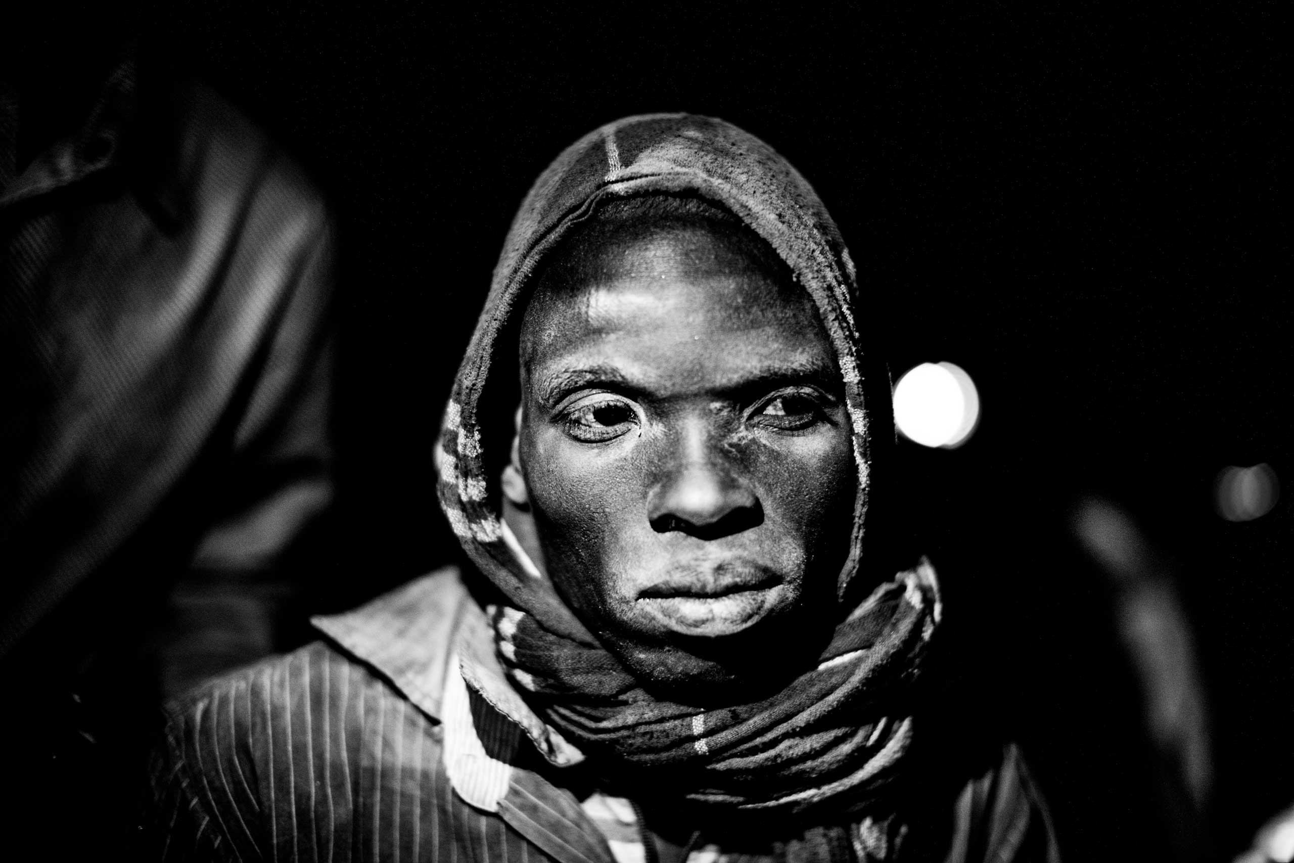 Dust covers the face of a young migrant headed to Libya.