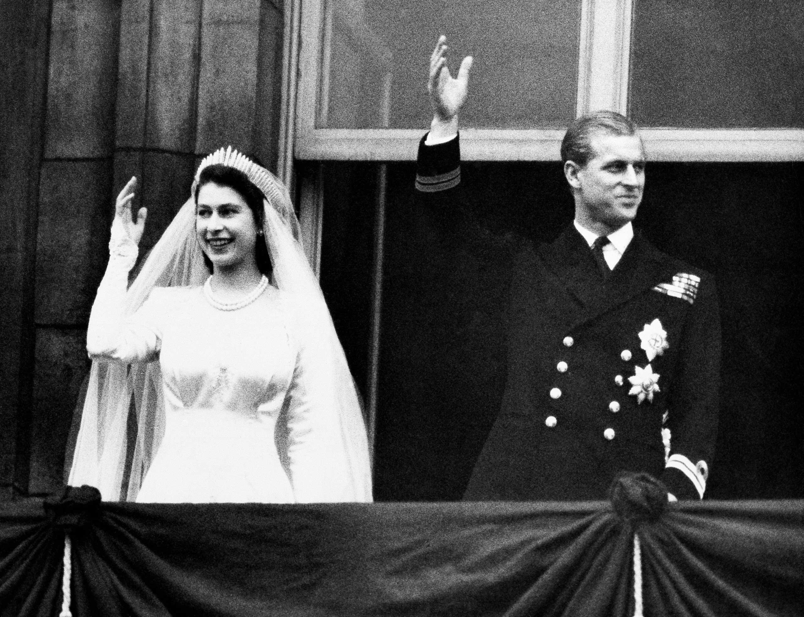 Princess Elizabeth and Prince Philip, Duke of Edinburgh wave to the crowds from the balcony of Buckingham Palace in London on their wedding day. Nov. 20,1947.