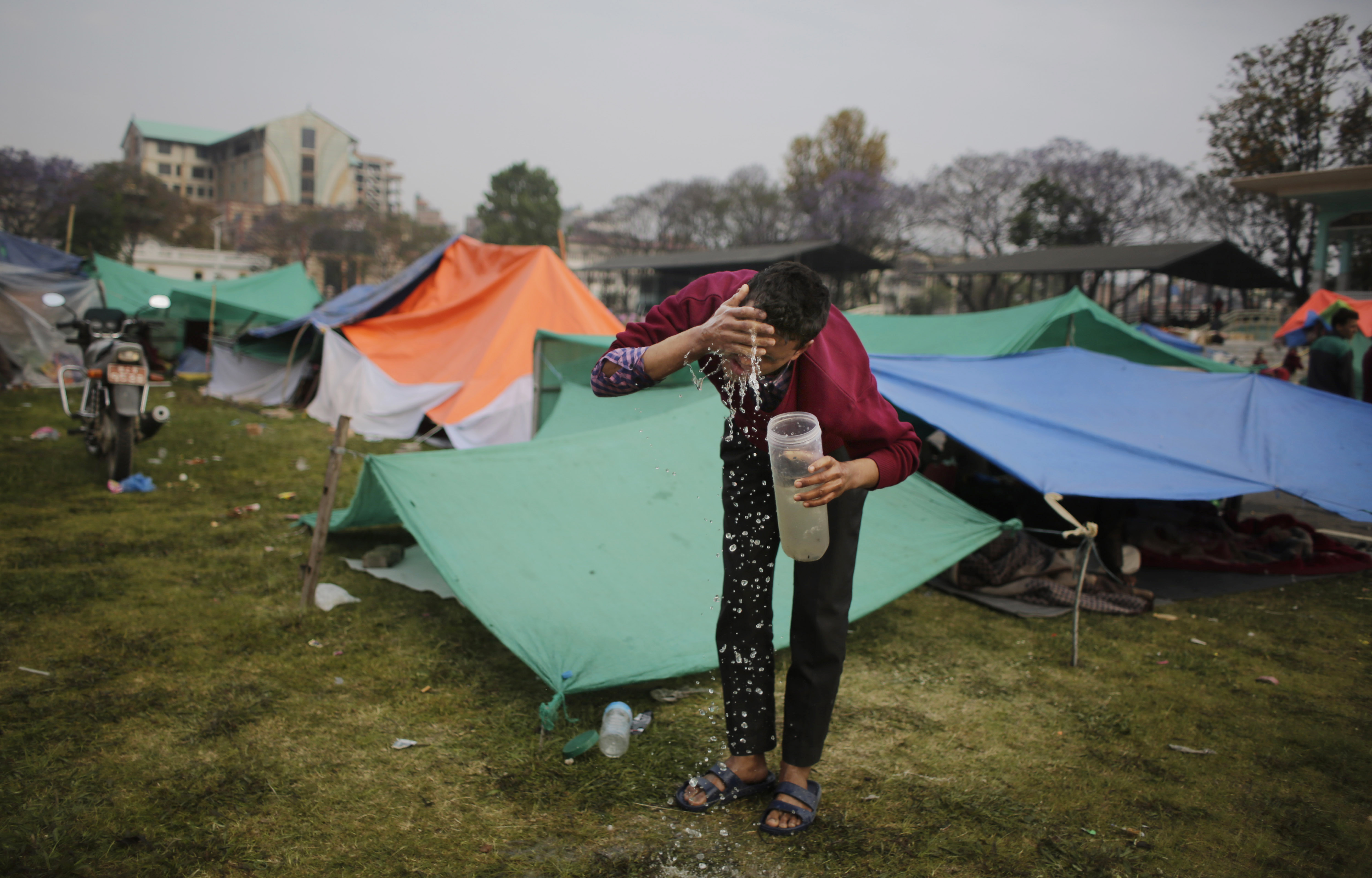 Survivor of Saturday's earthquake washes his face after spending night in an open ground from fears of earthquake tremors in Kathmandu, Nepal, Tuesday, April 28, 2015