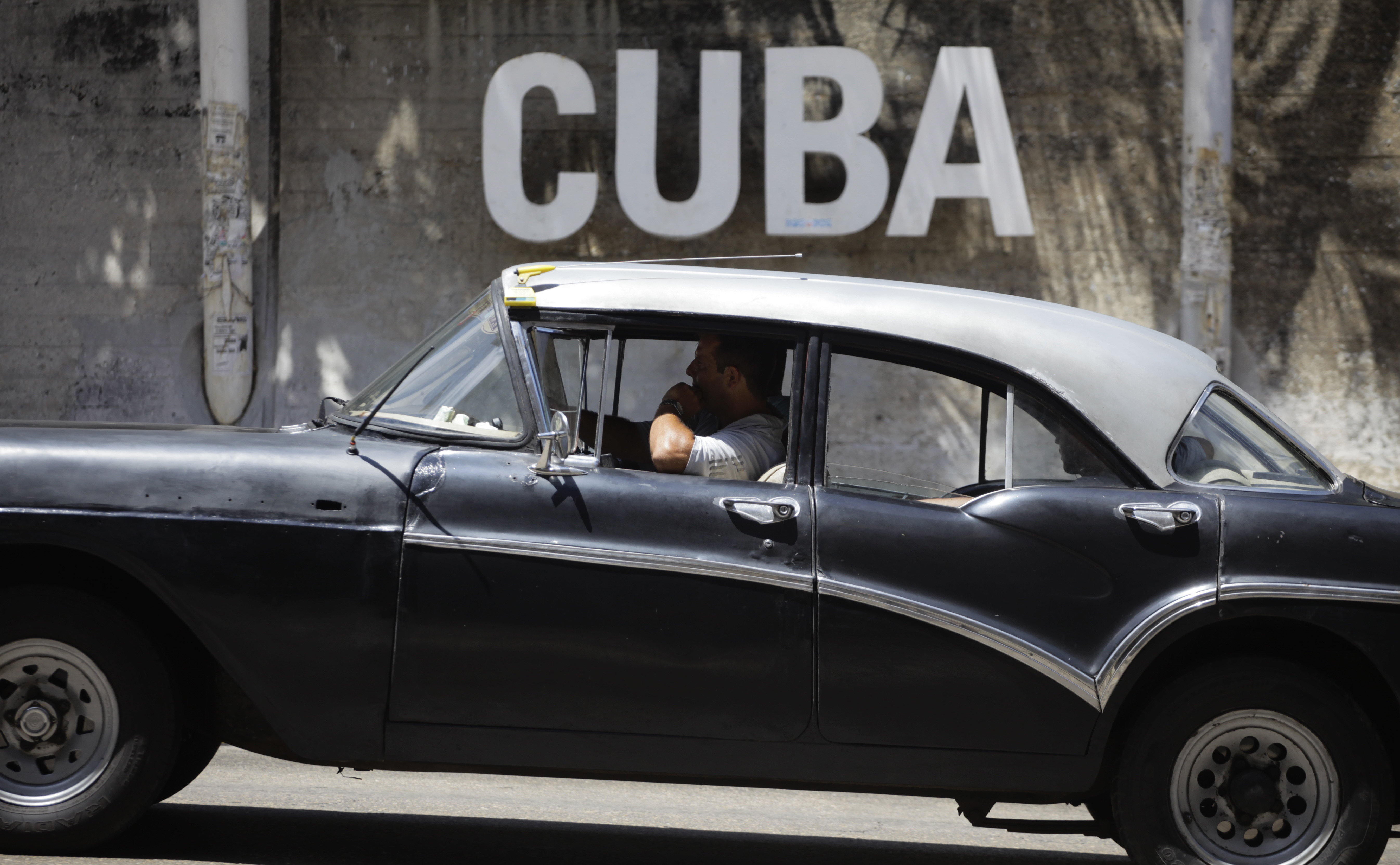 A man drives his taxi past a Cultural Center in Havana on April 14, 2015