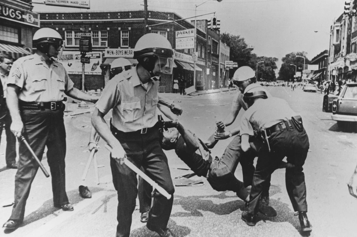 A man carried away by police during riots, Baltimore, Maryland, 1968.