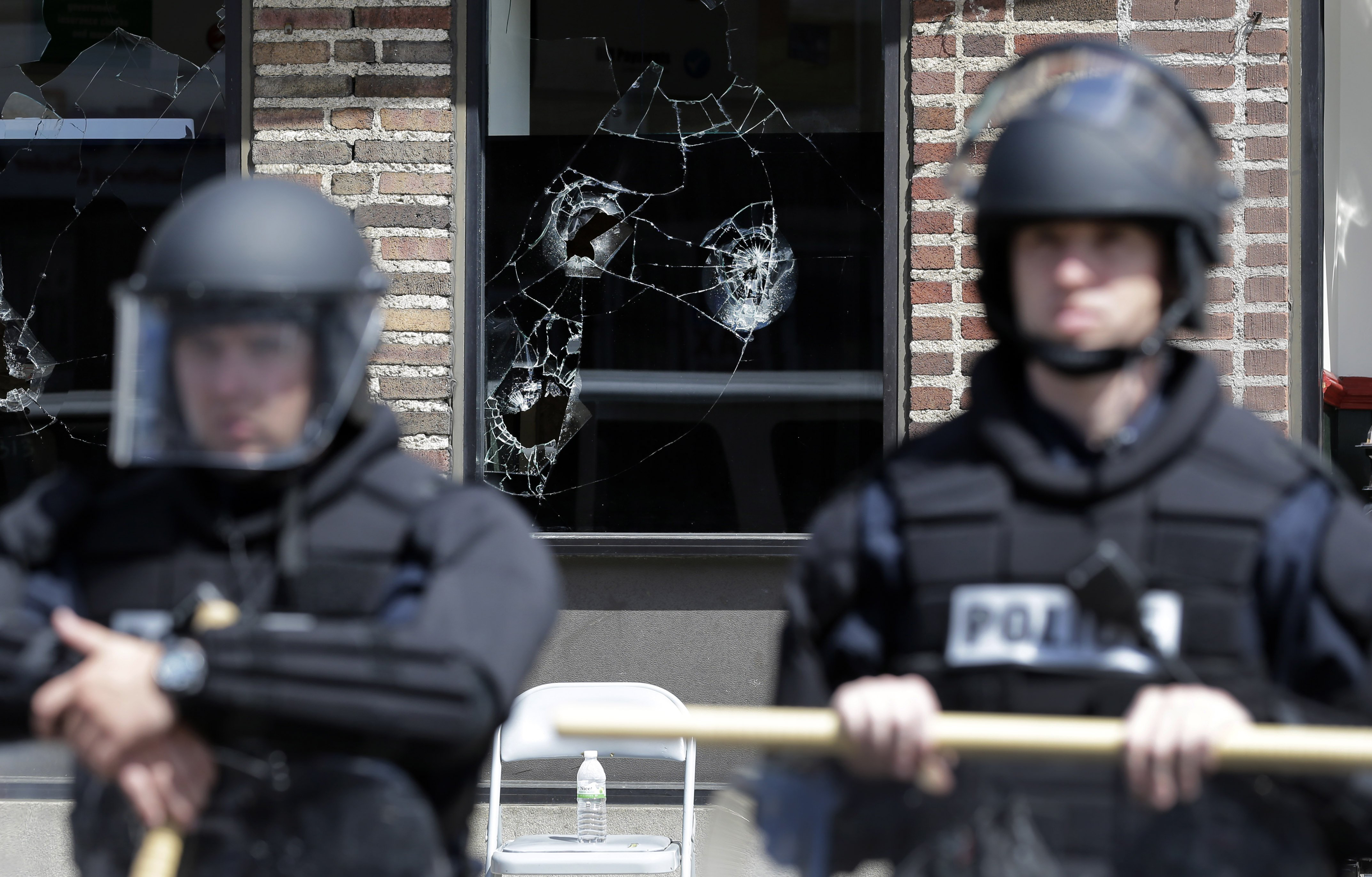 Broken store windows remain as members of the Anne Arundel County Police guard the intersection of North Avenue and Pennsylvania Avenue, on April 29, 2015, in Baltimore.