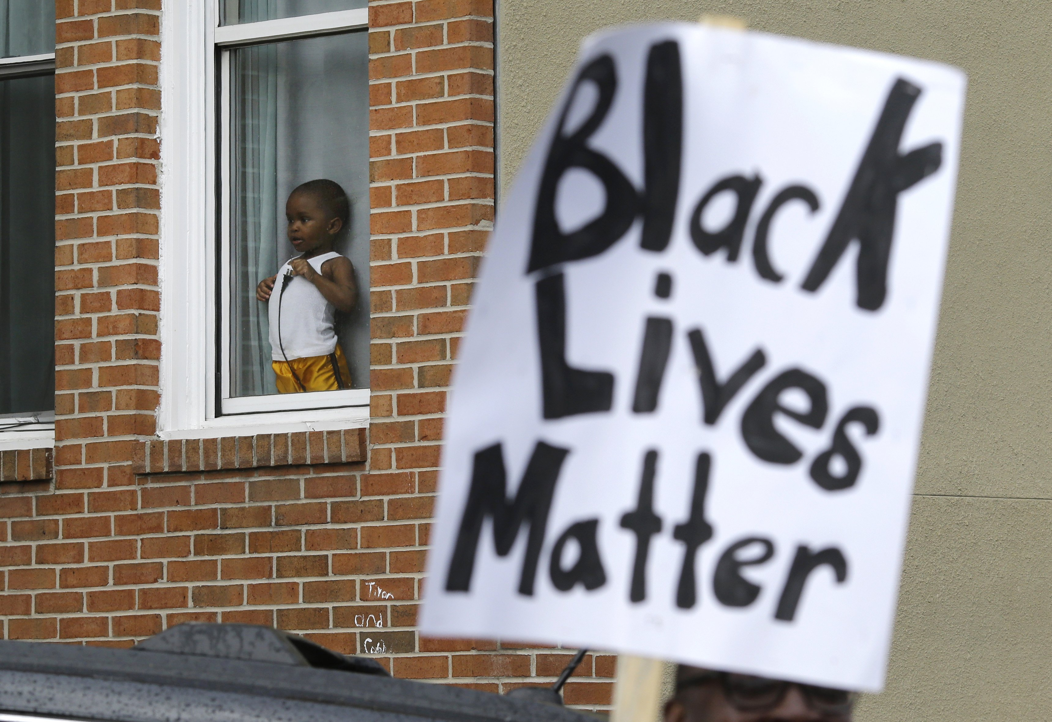 A child watches protesters march for Freddie Gray in Baltimore on April 22, 2015.
