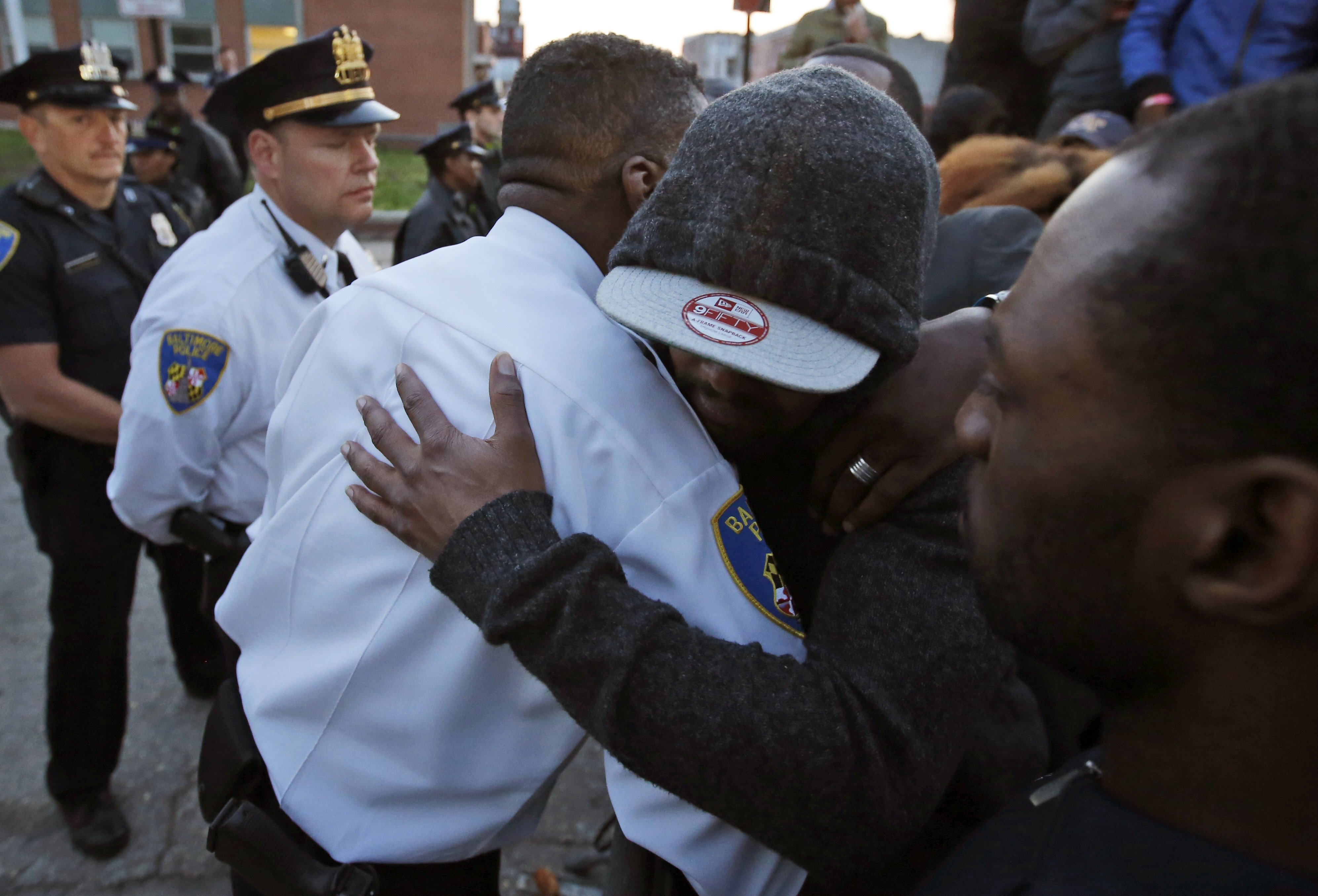 A marcher embraces Baltimore Police Lt. Col. Melvin T. Russell, in front of the department's Western District police station in Baltimore on April 22, 2015.