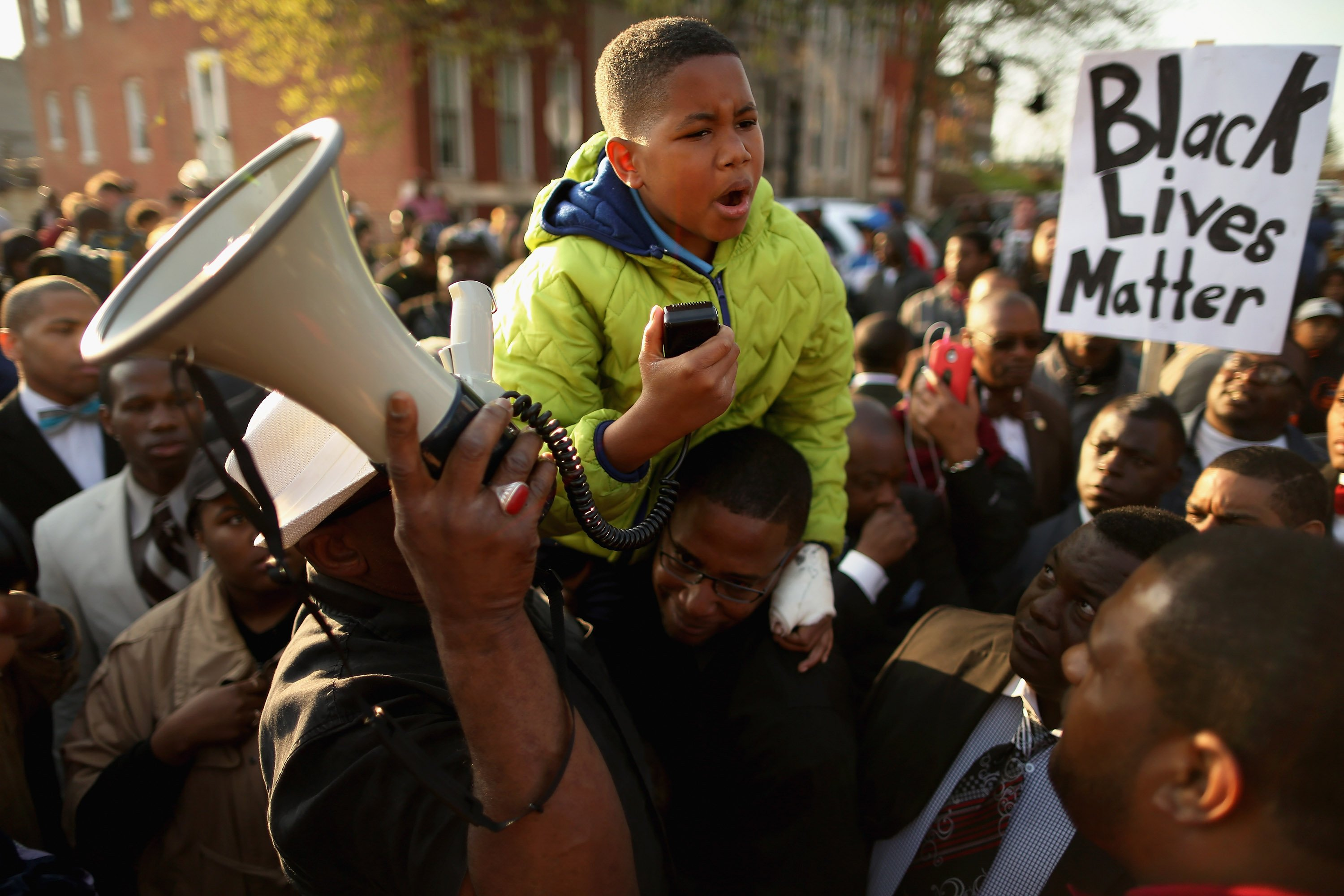 Ten-year-old Robert Dunn uses a megaphone to address hundreds of demonstrators during a protest against police brutality and the death of Freddie Gray outside the Baltimore Police Western District station in Baltimore on April 22, 2015.
