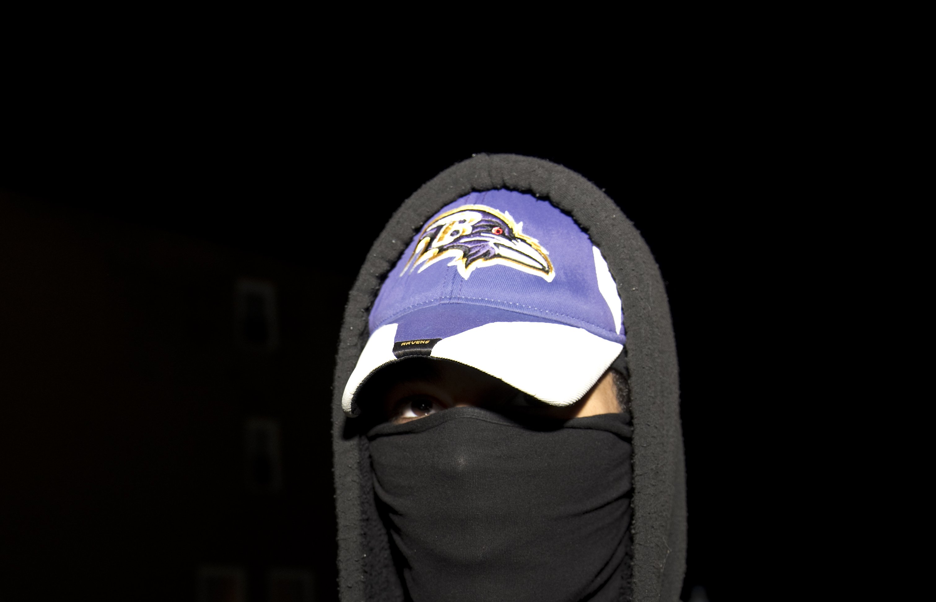 A protester wearing a Baltimore Ravens cap covers his face during a rally for Freddie Gray outside Baltimore Police Department Western District station in Baltimore on April 22, 2015.