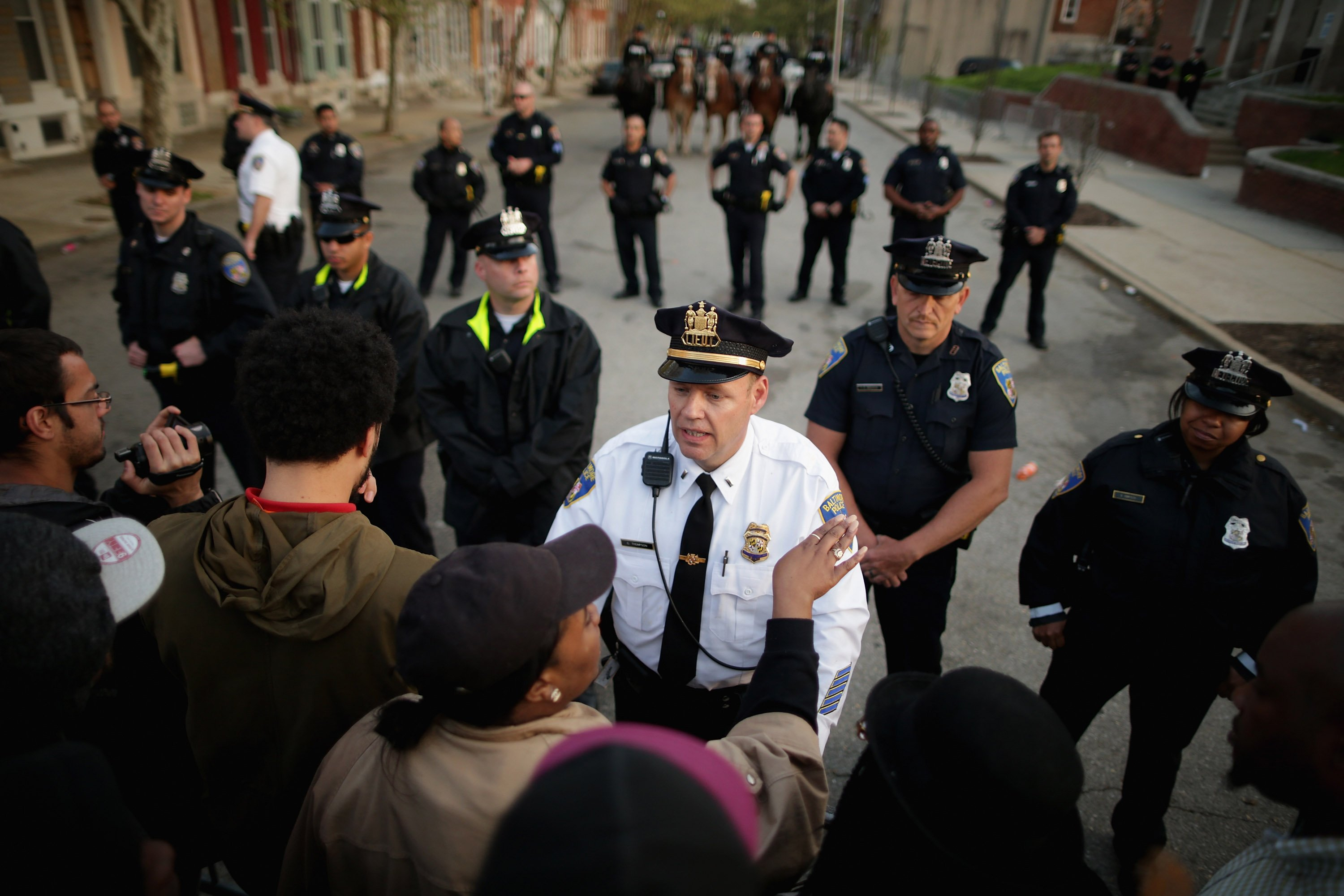 Protesters argue with Baltimore Police officers outside the Western District police station in Baltimore on April 22, 2015.