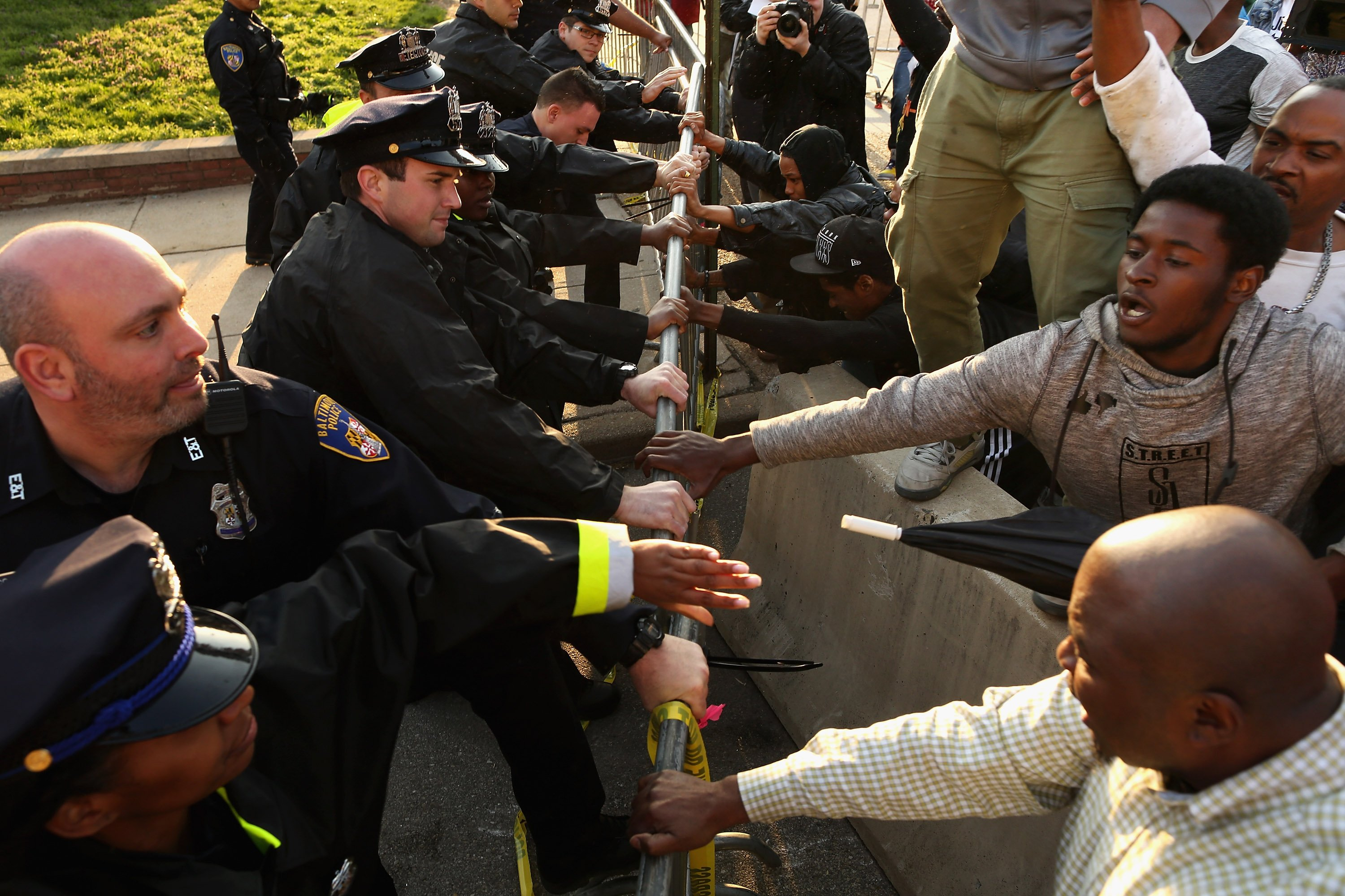 Demonstrators and police officers wrestle over a metal barricade outside the Baltimore Police Western District station in Baltimore on April 22, 2015.